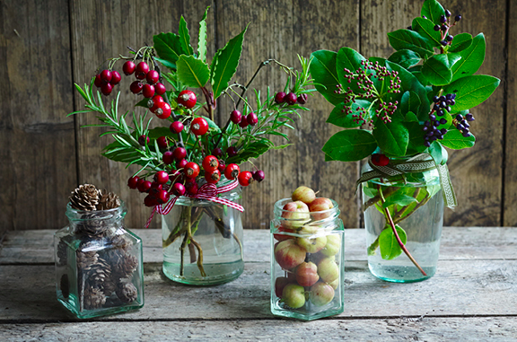 Any jars or bottles around the house can be filled with foliage, berries and even apples can make it look festive. I like them in clusters as they make more impact.