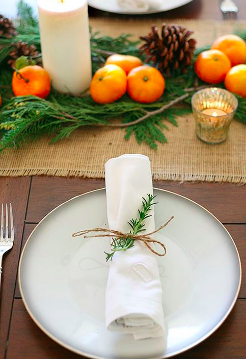 A sprig of rosemary tied around a white napkin with some twine, looks unpretentious and natural. The satsumas, foliage, candles and pine cones make a cheerful centre piece.