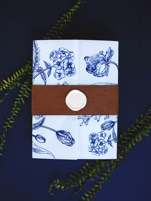 The navy letterpress wedding invitation was wrapped in a digitally printed navy botanical vellum sheet, kept closed with a cognac leather belly band and white personalized wax seal.