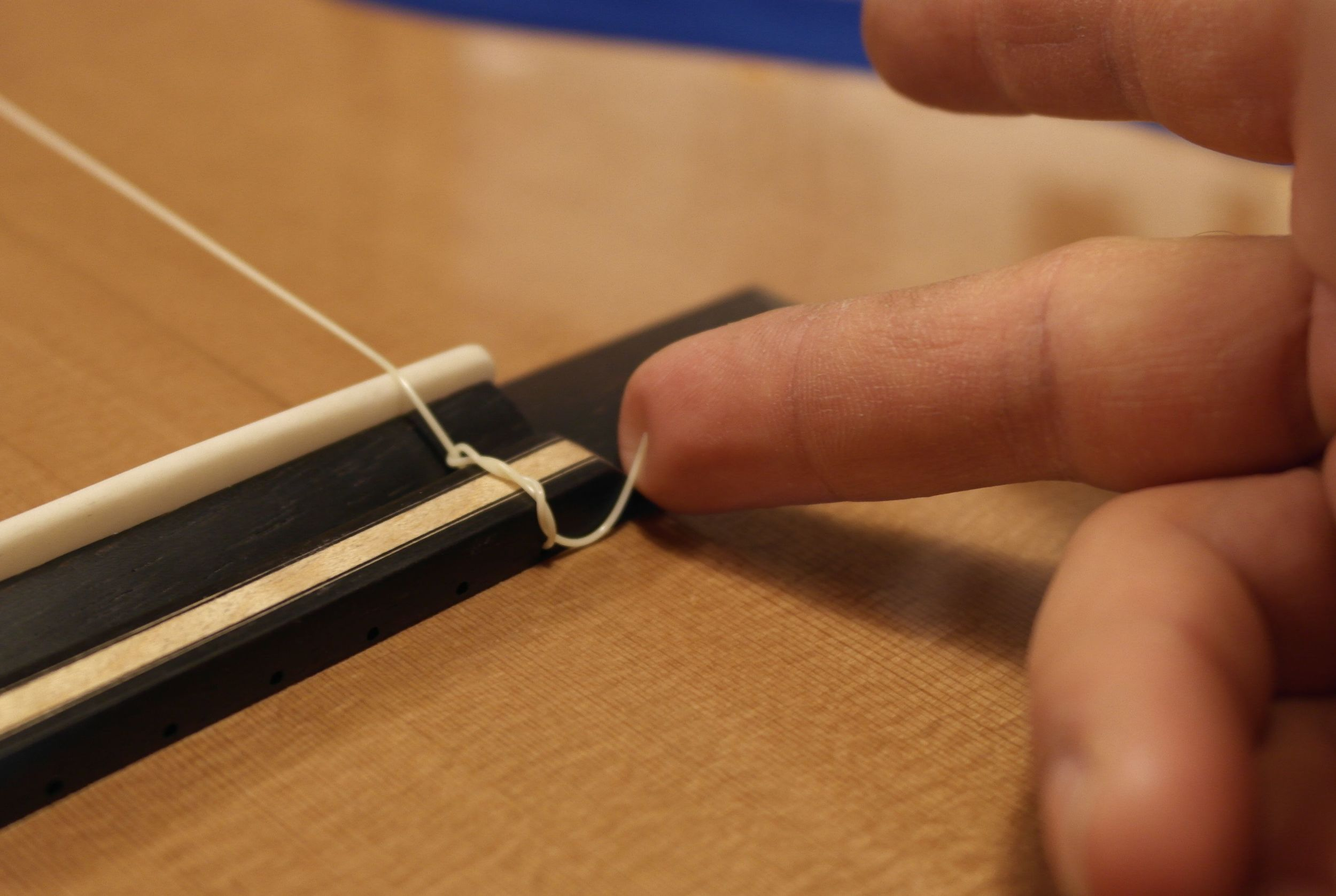 Make sure the string end is locked against the rear faceof the tie block and noton top or else it will slip.