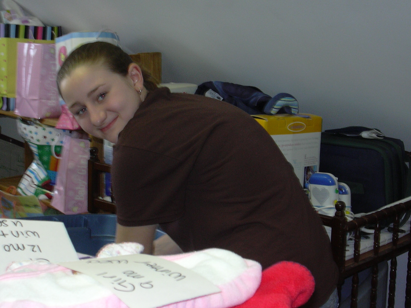 Rachel as a high school student sorting through baby items for our Boutique.