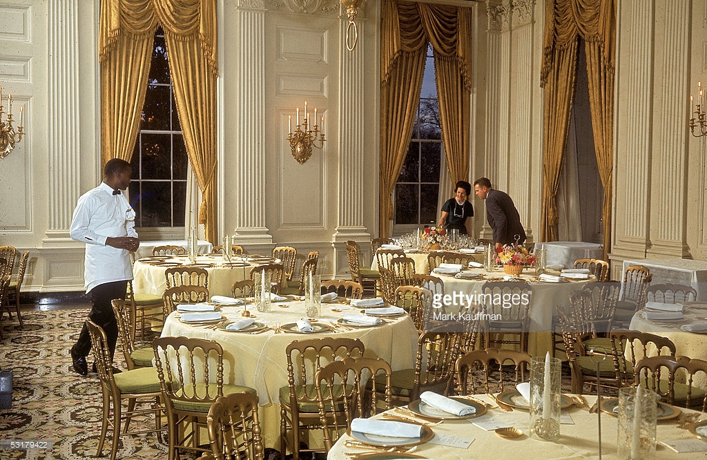 1965 - First Lady Lady Bird Johnson inspecting tables prior to a dinner for Princess Margaret. Image via Getty Images.