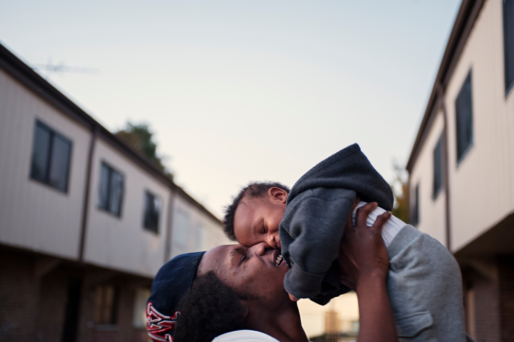A rare sight in the circle, a father spends time with his son on the front stoop of their home at Jericho Circle.