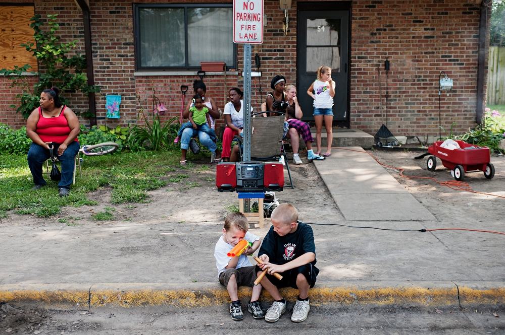 Kids play on the curb during a cookout after the memorial service for resident Arlissa Dockery's husband, Larry Pryor who died of cancer. Speculation in the community is that he contracted the cancer from the lead in pipes of his home at Jericho Circle.