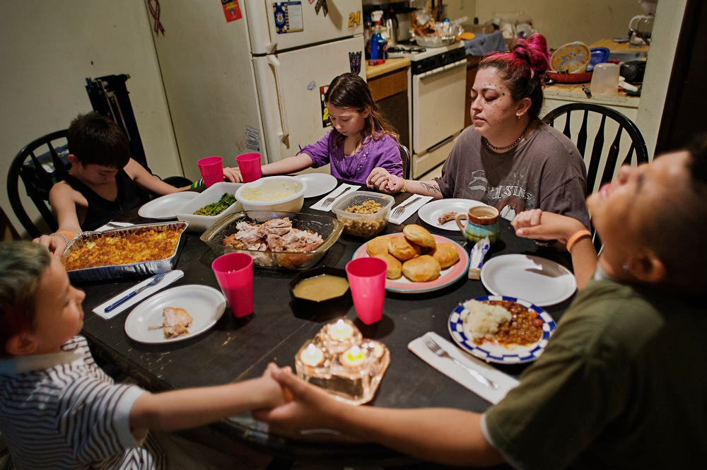 The Carvell family holds hands as they gather around the table for Thanksgiving dinner.