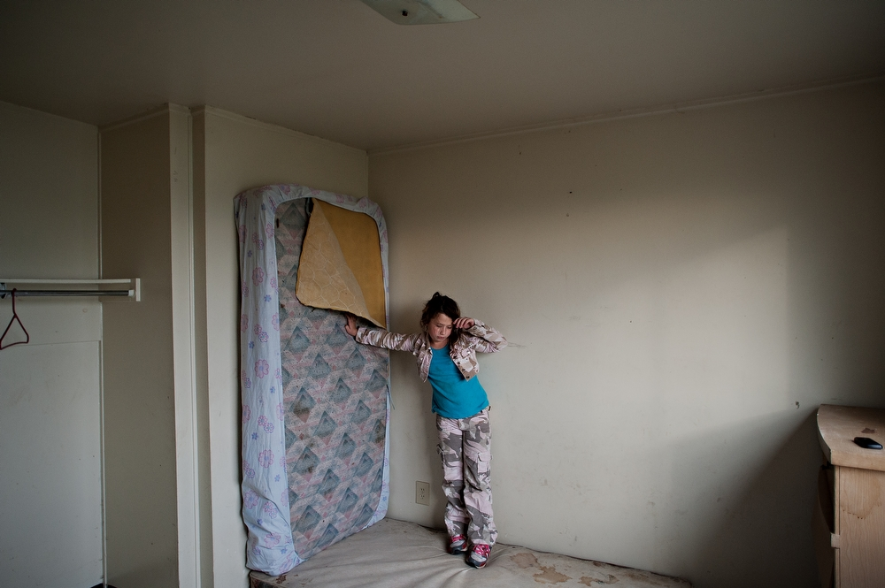 """Salena Carvell holds up her bed as she packs up her room and moves out of her families home in Jericho Circle. """"I'm sad to leave all my friends,"""" Carvell said."""