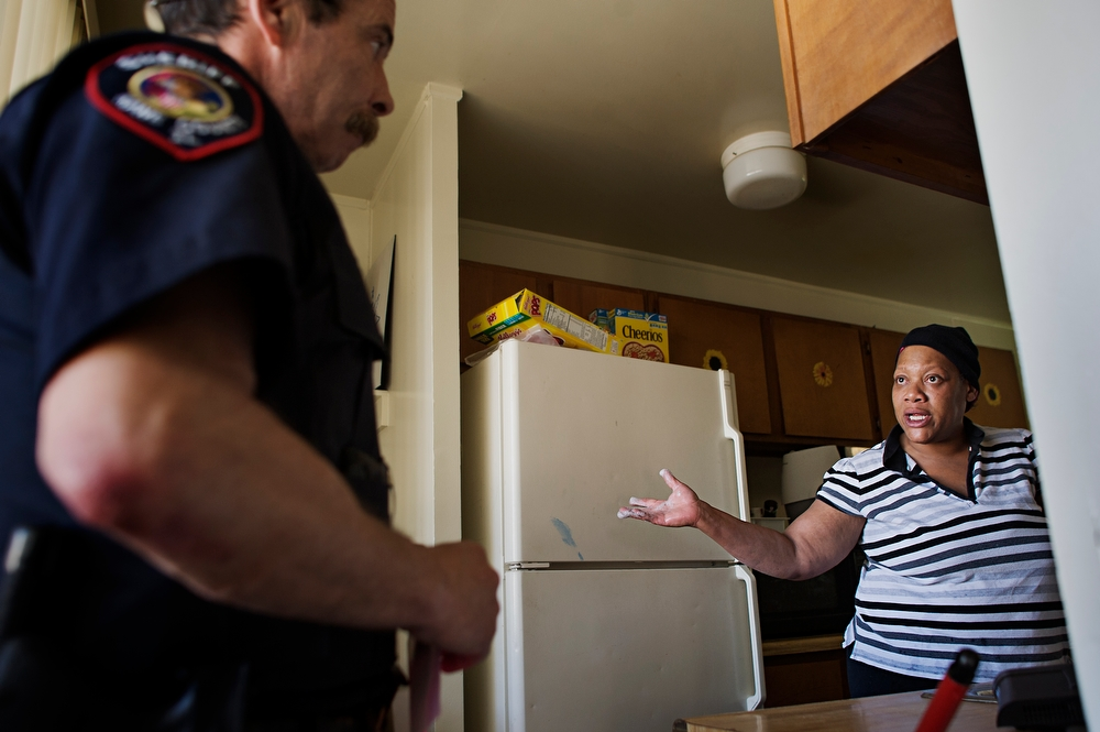 Letitia Mendenhall talks to Kane County Sheriff Deputy Jim Seidelman, left, after he explained how the eviction was going to work. Mendenhall lost her good standing status with the Aurora Housing Authority after a conflict with ComEd in December of 2010.