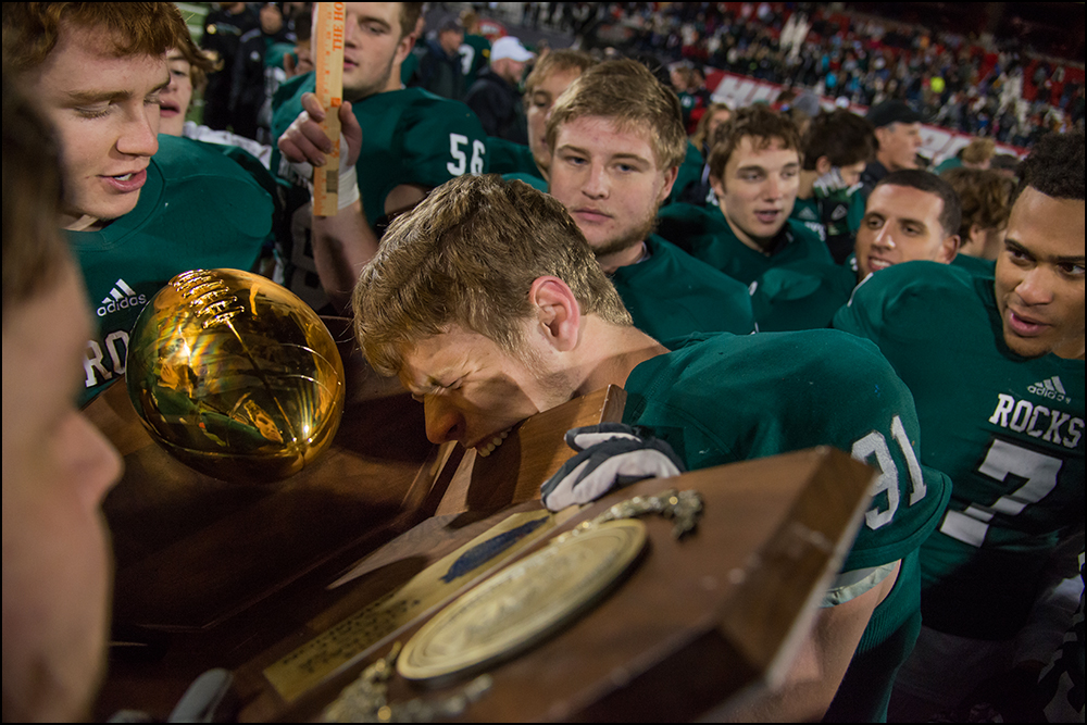 Trinity's Landon Corolla bites the championship trophy after the Shamrocks defeated Dixie Heights 47-14 during their KHSAA Commonwealth Gridiron Bowl game at Western Kentucky University in Bowling Green, KY on Saturday, December 6, 2014. Photo by Brian Powers