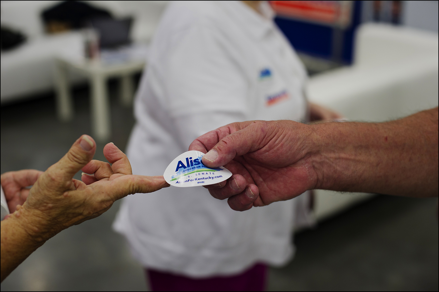 Supporters of U.S. Senate candidate Alison Lundergan Grimes pick up stickers at the Democrats booth inside the the Kentucky State Fair in Louisville, KY on Thursday, August 21, 2014. Photos by Brian Powers