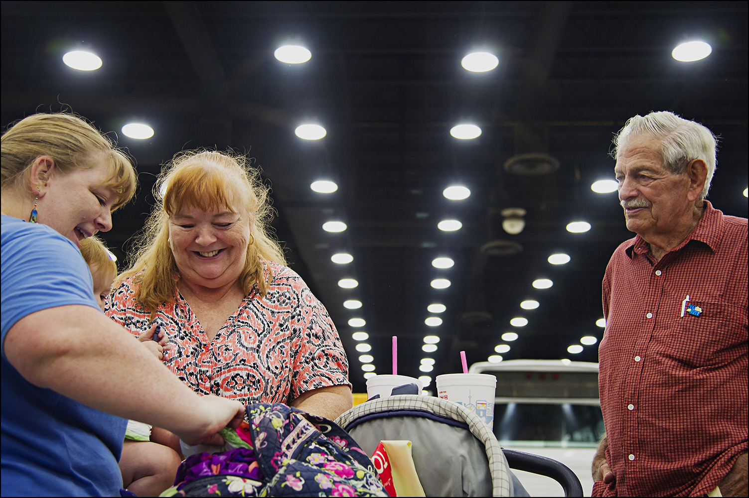 Louisville resident Amanda Mayhew, left, and her mother Teri Eisenmenger, center, finish changing Mayhew's daughter, Caramia's diaper during the Kentucky State Fair in Louisville, KY as her grandfather, Berlin Cook watches on Thursday, August 21, 2014. Photos by Brian Powers
