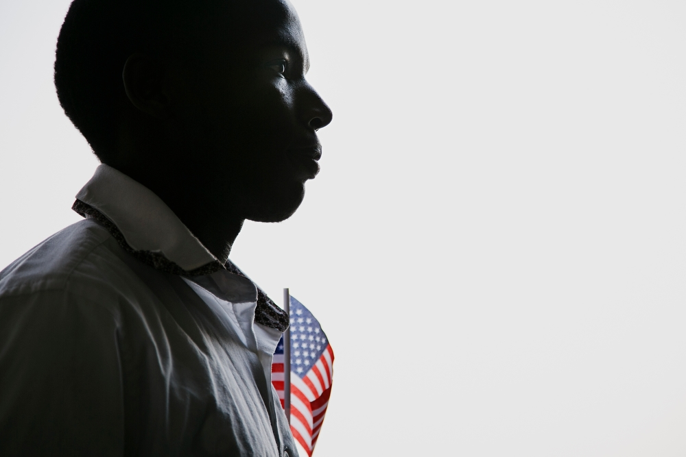 Alex Degoce Niyonyinshu, 23 from Burundi, waits in line before walking out onto the field at Principal Park for a naturalization ceremony to 30 new United States citizens from 14 different countries in Des Moines on Friday, July 3, 2015. Niyonyinshu has lived in Des Moines for the past seven years.