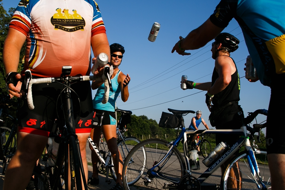 Riders pass out free beer that a supporter left at the end of their driveway for cyclists on the way to Coralville during RAGBRAI on Friday, July 24, 2015.