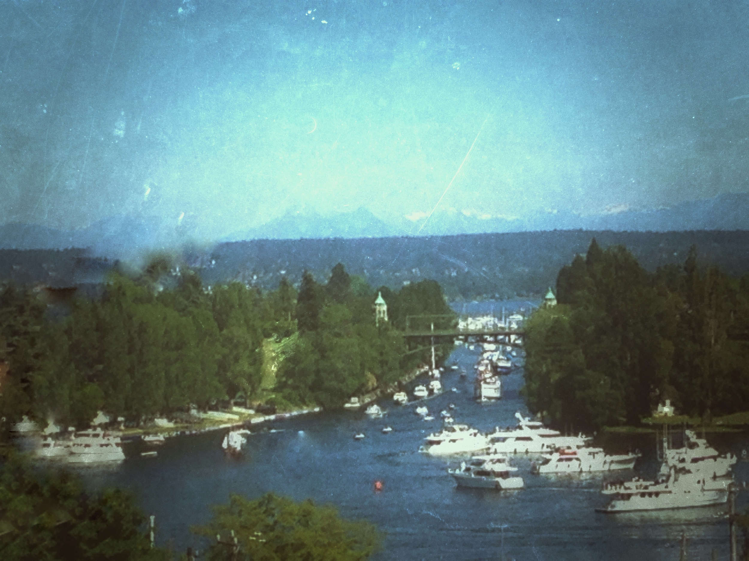 Opening Day, May 7, 2016. Portage Bay (foreground), leading into the Montlake Cut, connecting to Lake Washington. Cascade Mountains in the distance.  The Seattle Yacht Club (not seen here) is to the right.