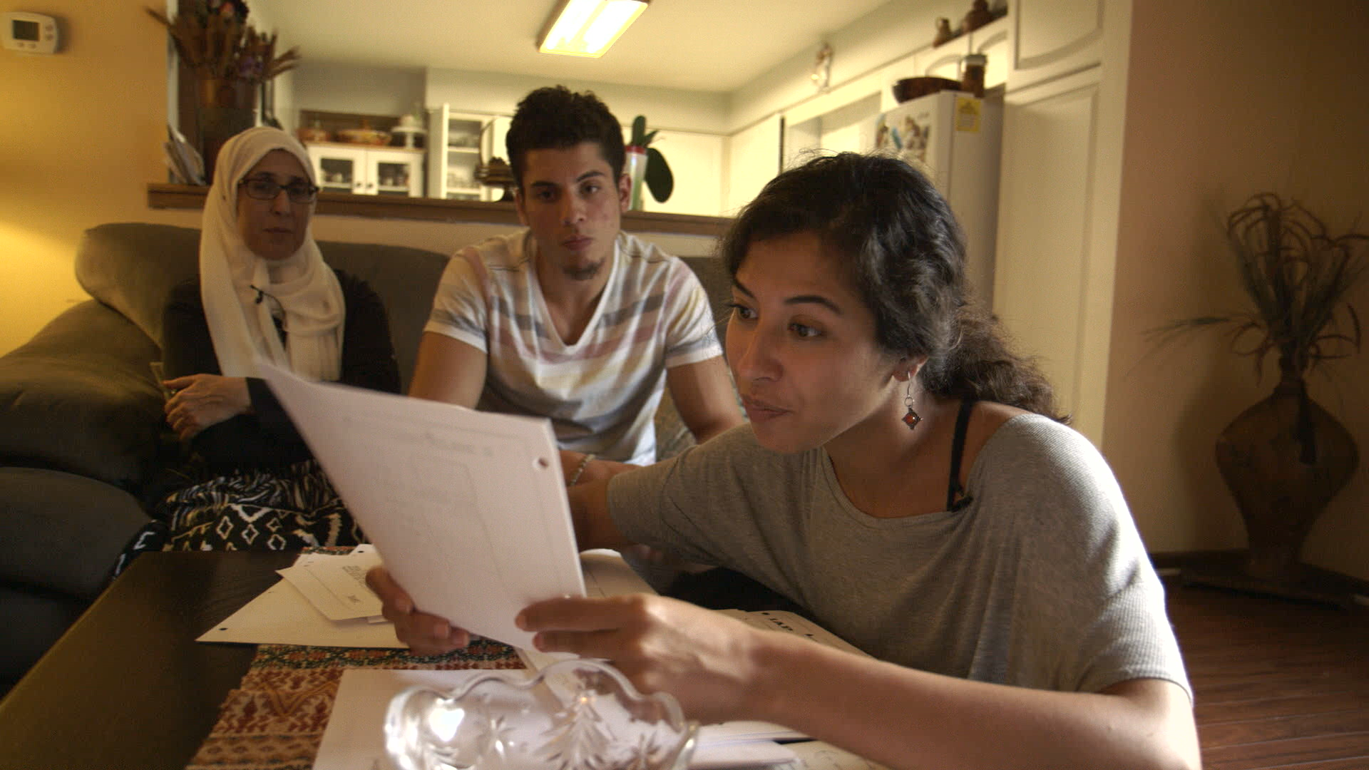 4. The Feeling of Being Watched - Assia shows FBI documents to her family.png
