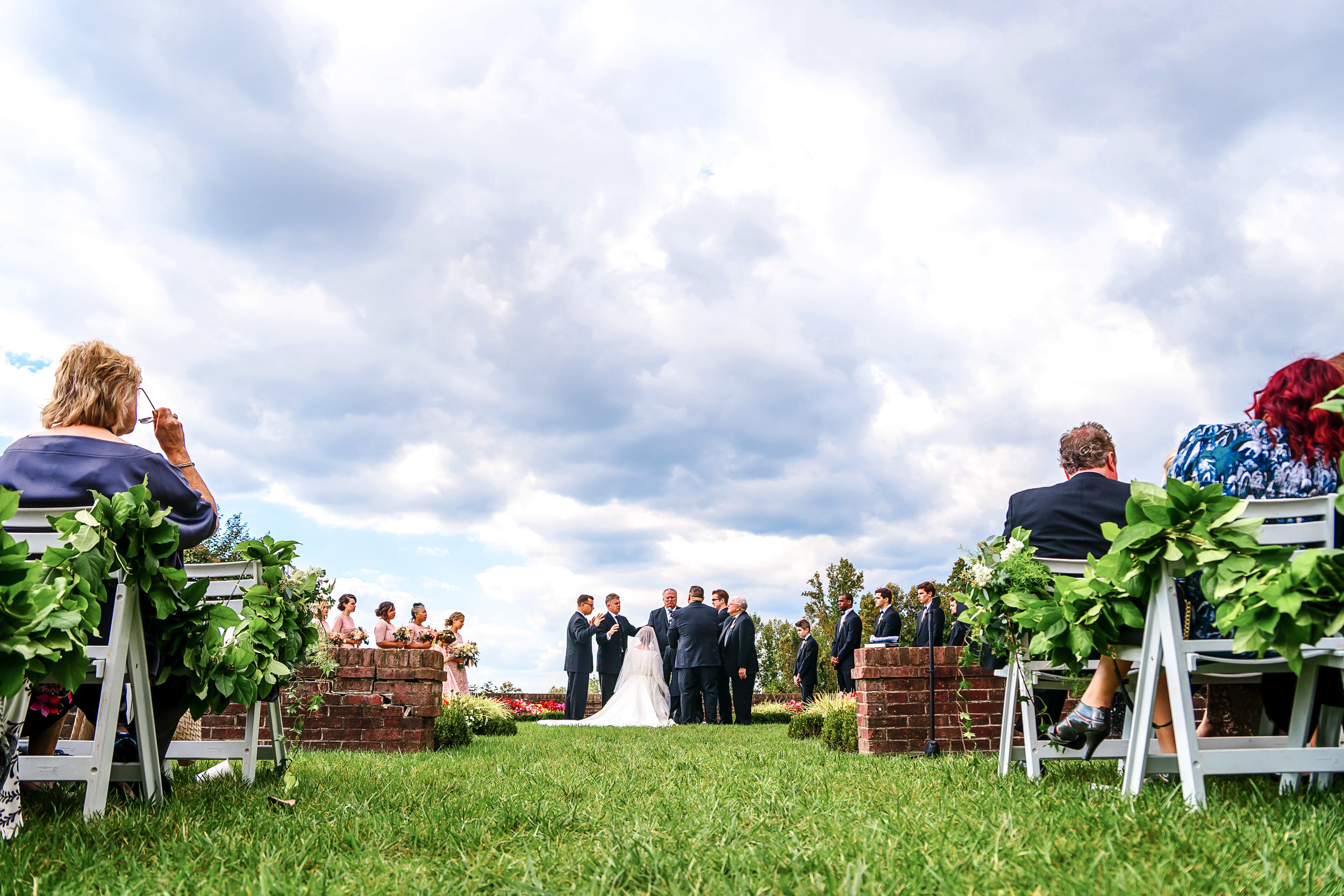 Dramatic clouds wedding ceremony photo at Oxon Hill Manor by Jessica Nazarova