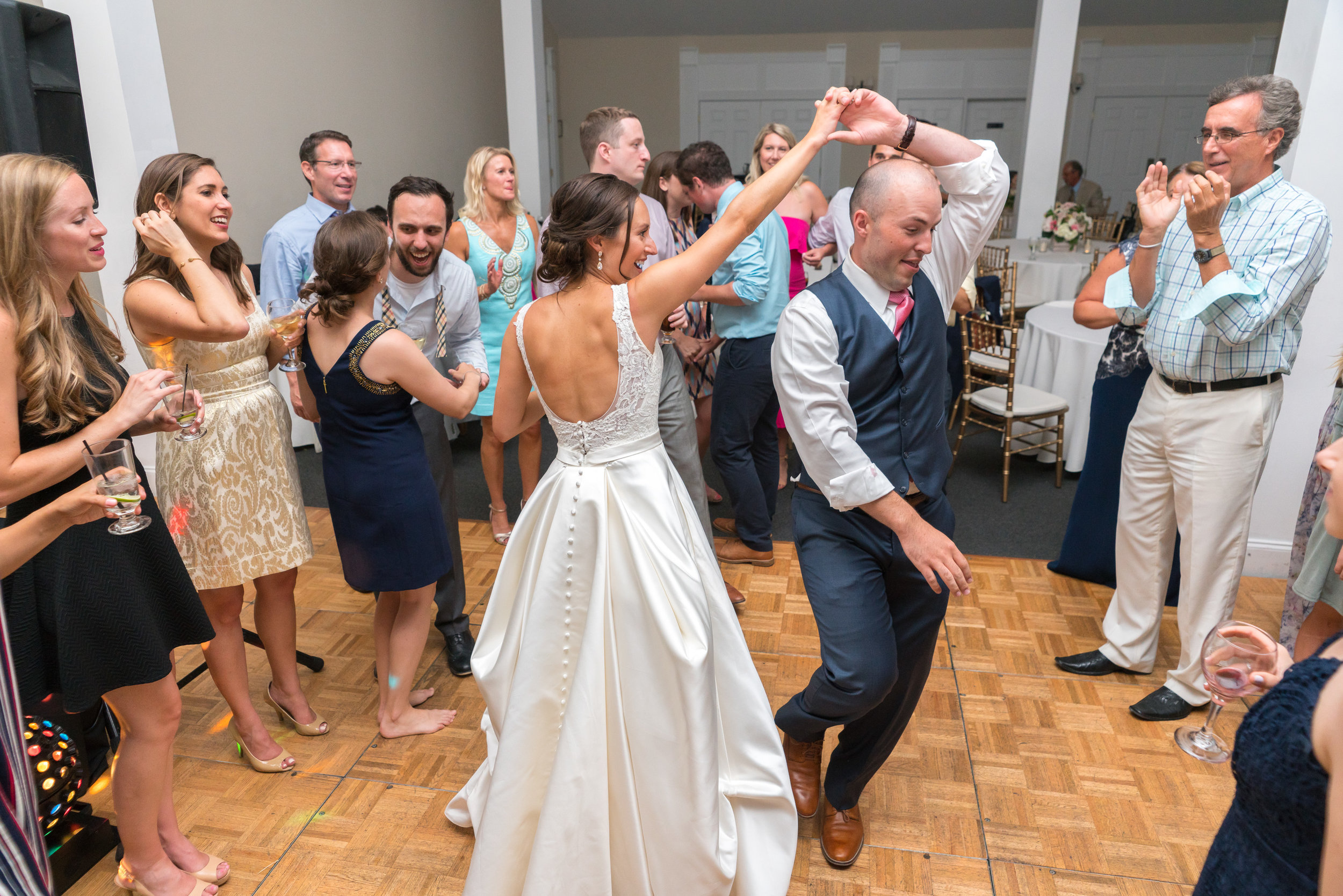 Bride and groom dancing in a group at Springfield Manor Winery