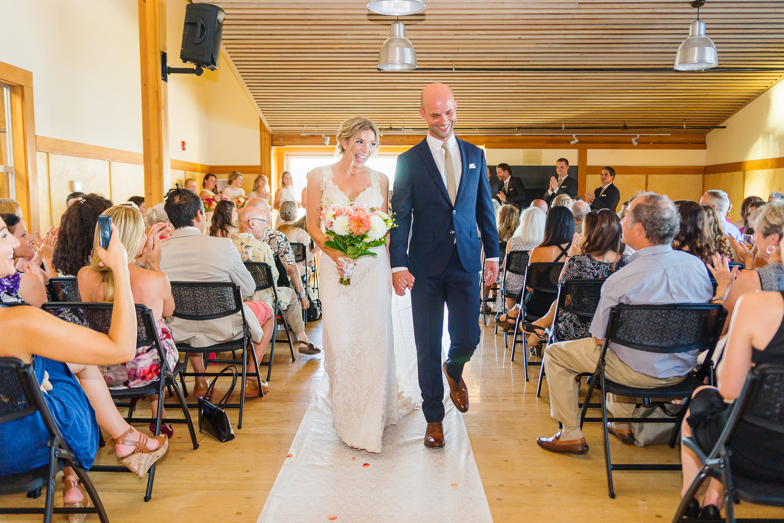 Bride and groom walking down the aisle at mt baker rowing sailing center