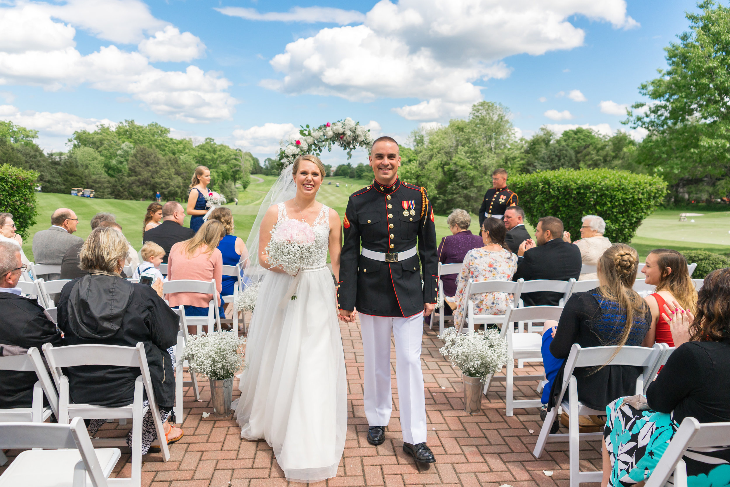 Bride and groom walking down the aisle at their summer golf course wedding