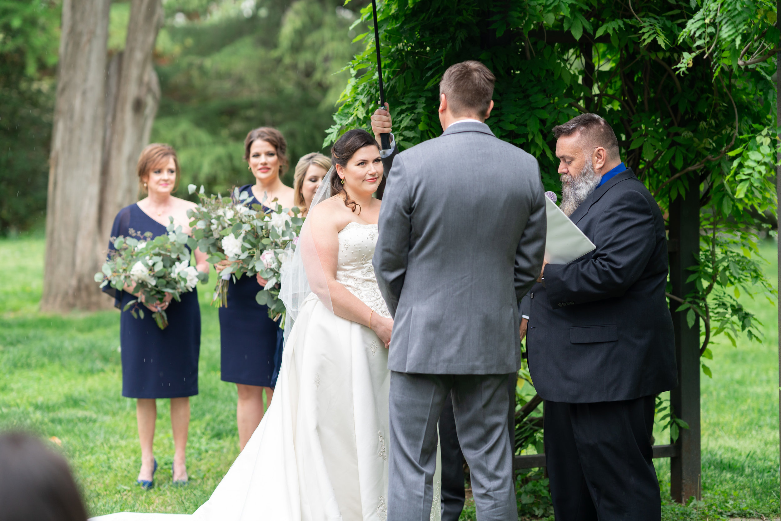 Ceremony under an ivy arch at Hendry House wedding