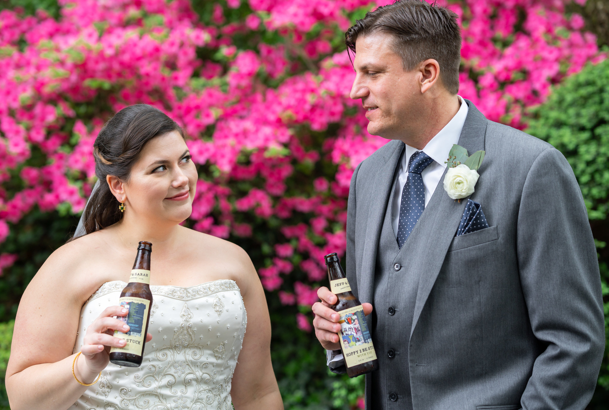 Bride and groom toasting with beer bottles with custom wedding day labels