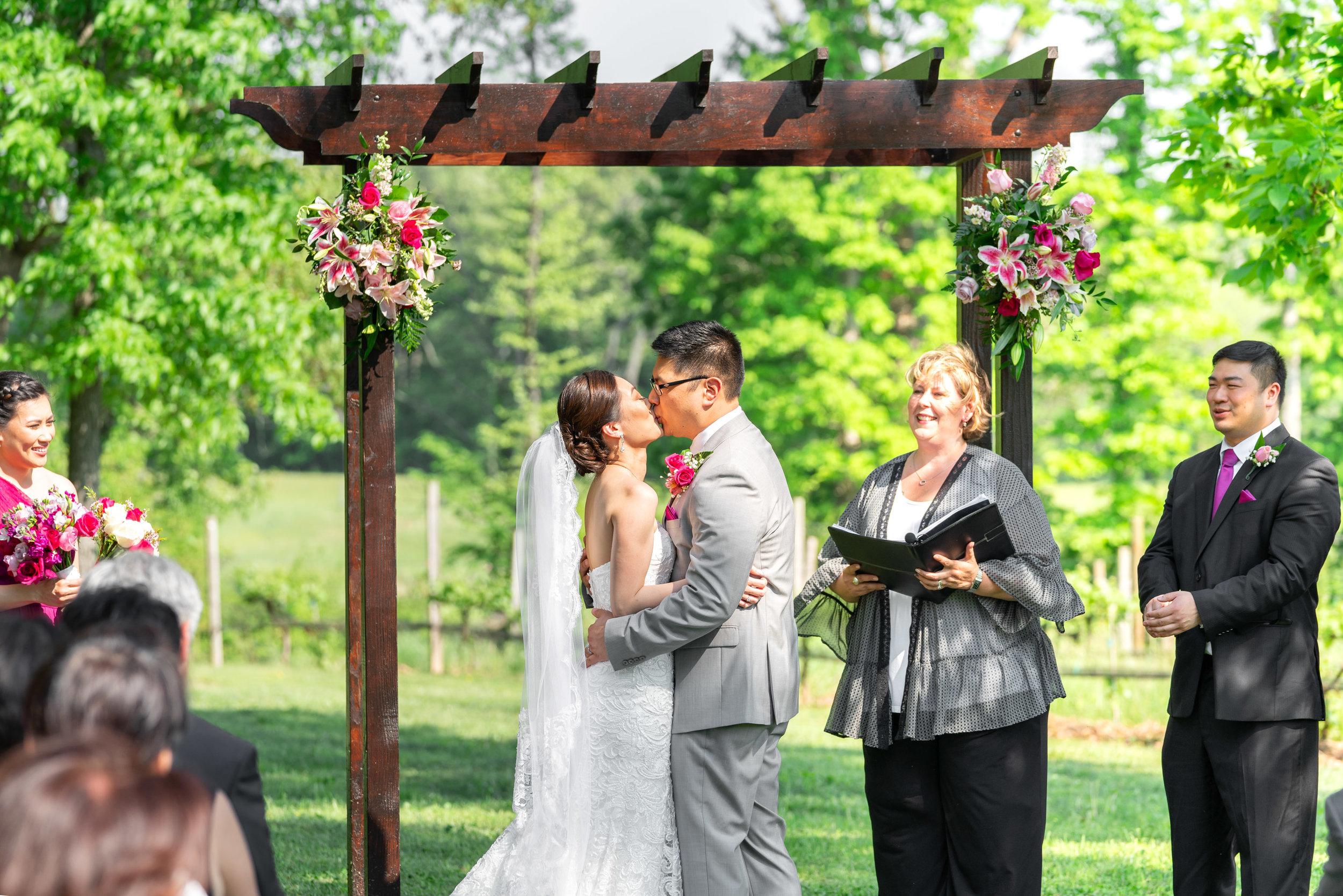 Bride and groom kiss under arch at Harvest House Lost Creek Winery