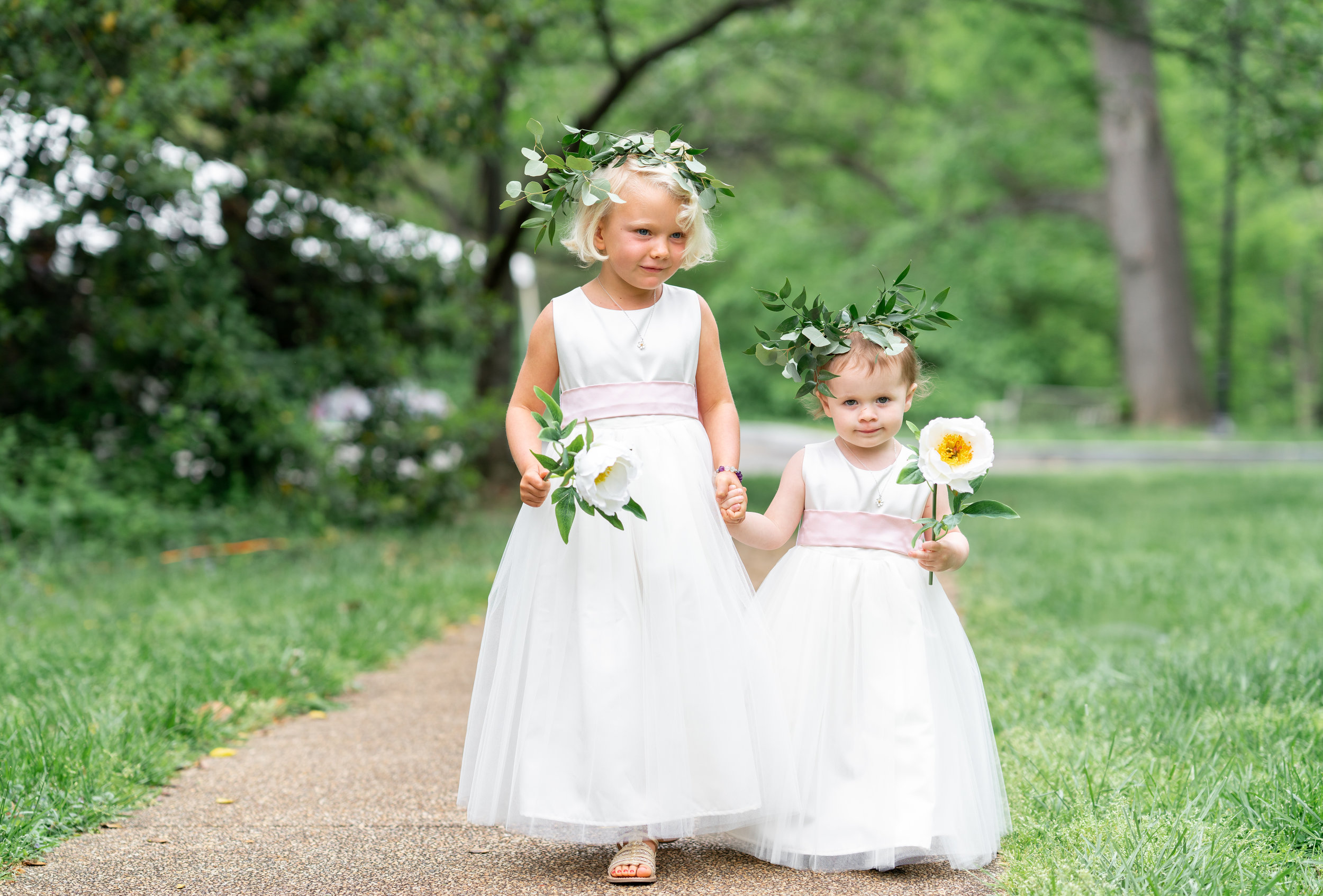 Flower girls in flower crowns walking down the aisle at Hendry house wedding