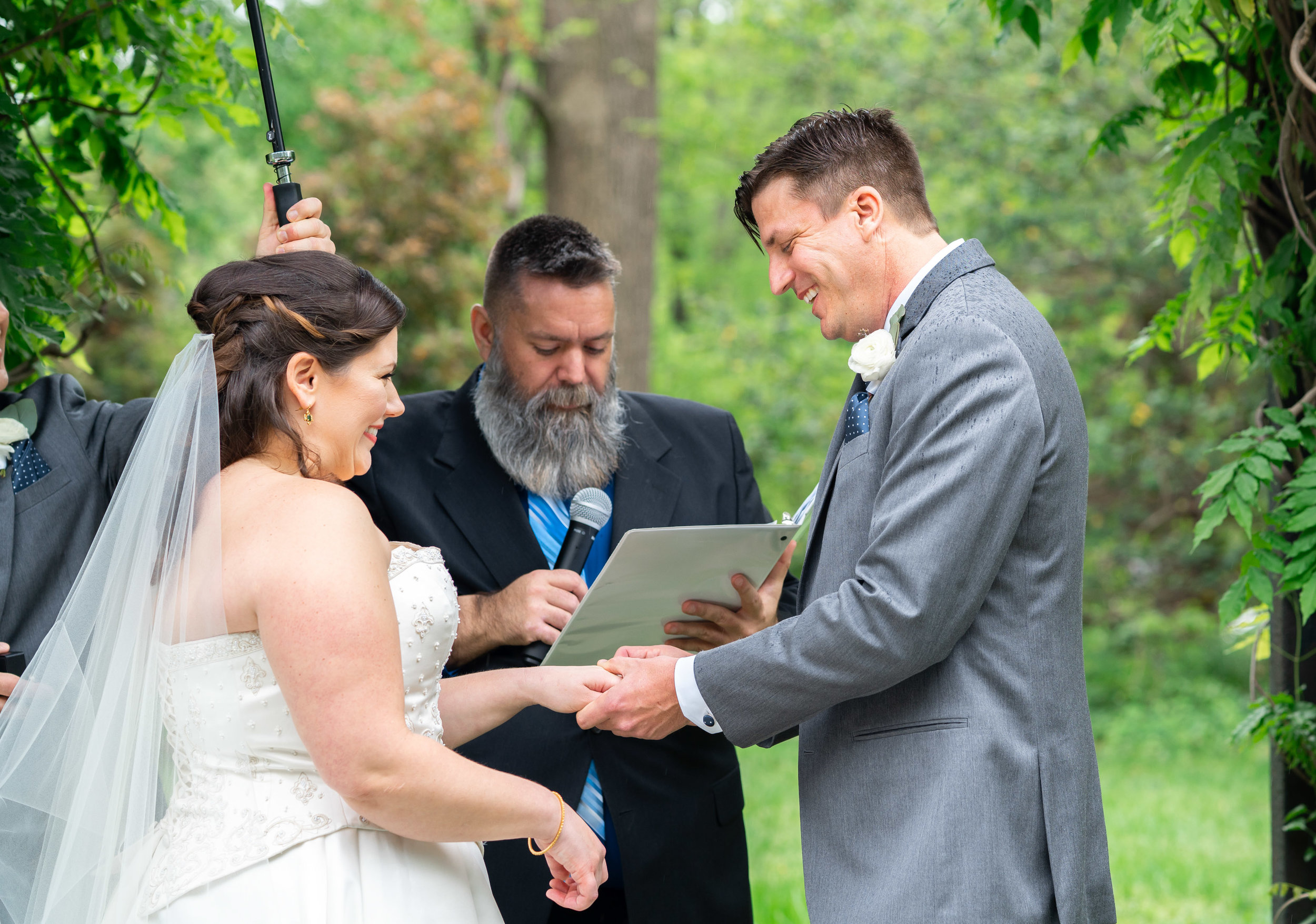 Bride and groom smiling during ceremony under ivy arch at Hendry House wedding