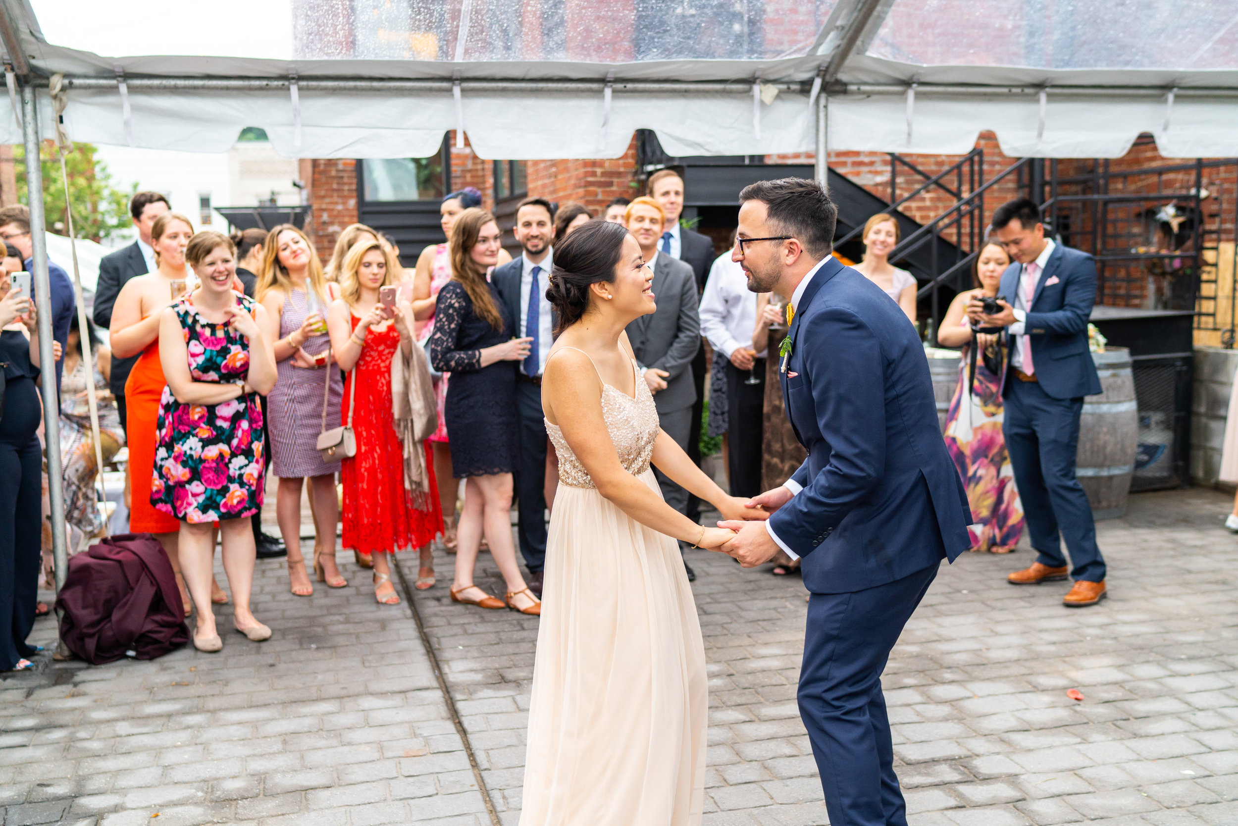 Bride and groom laugh while sharing first dance under clear tent reception at DC venue Gallery O on H
