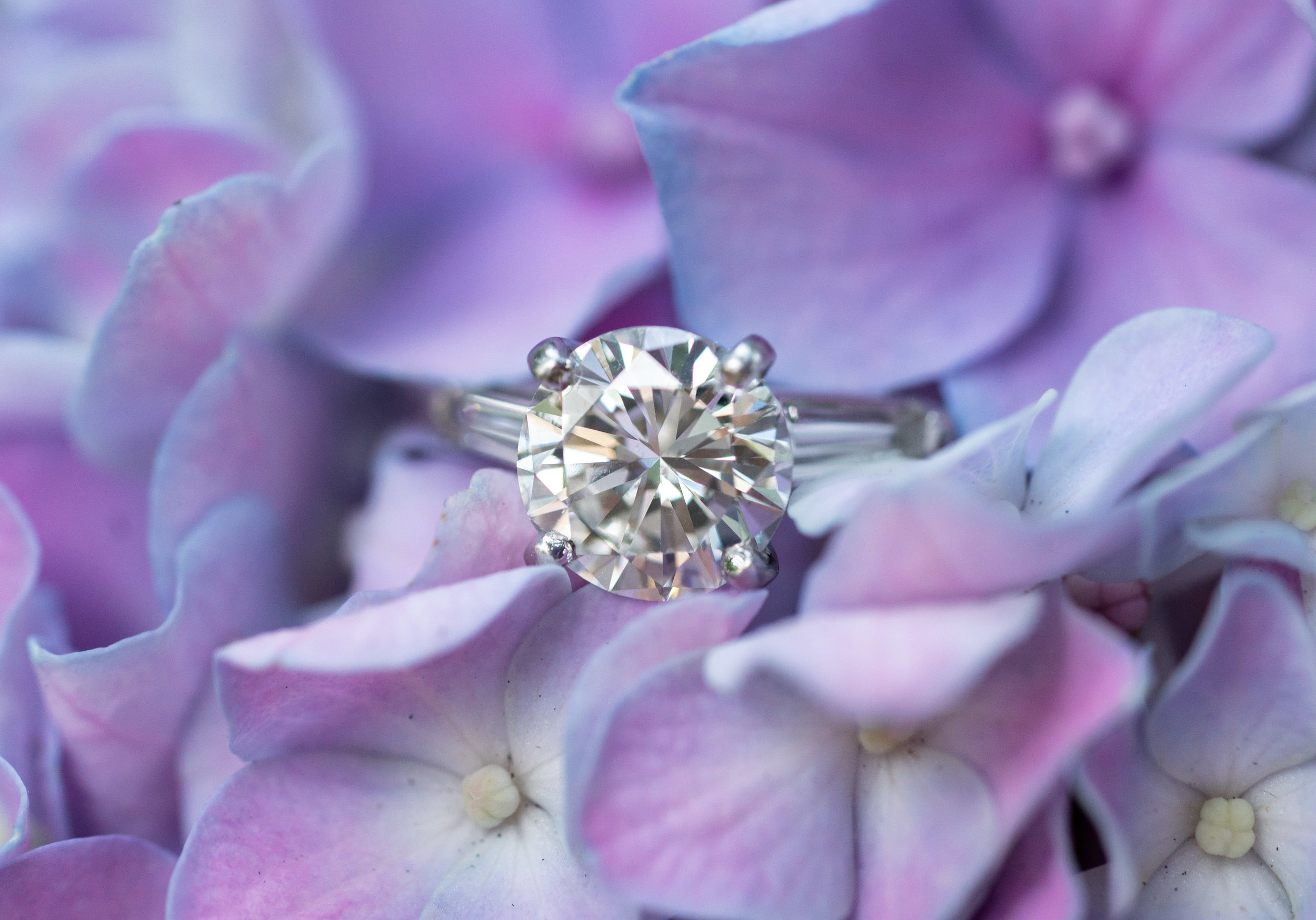 Four prong round cut solitaire with art deco baguettes on the side