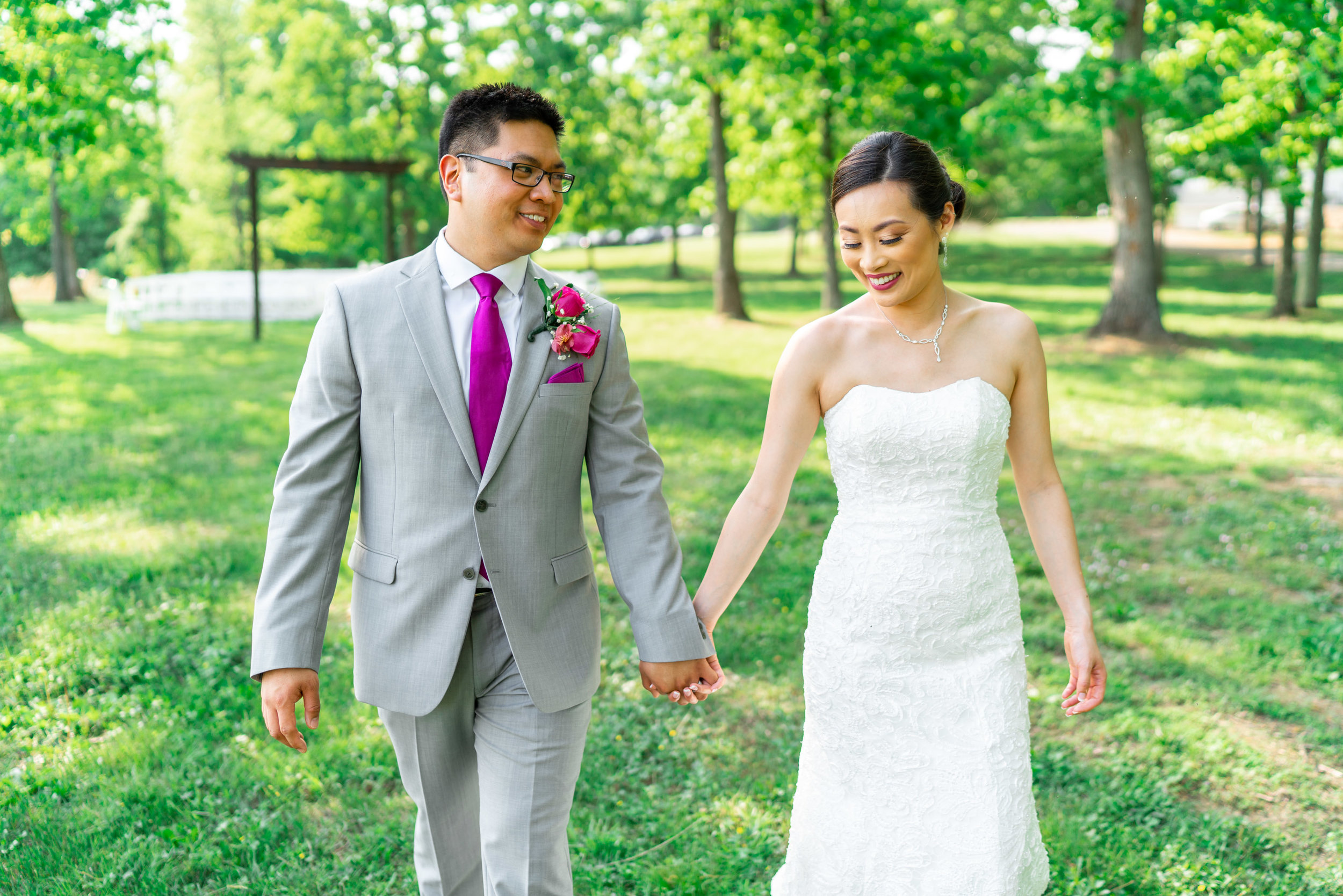 Bride and groom walking and holding hands smiling