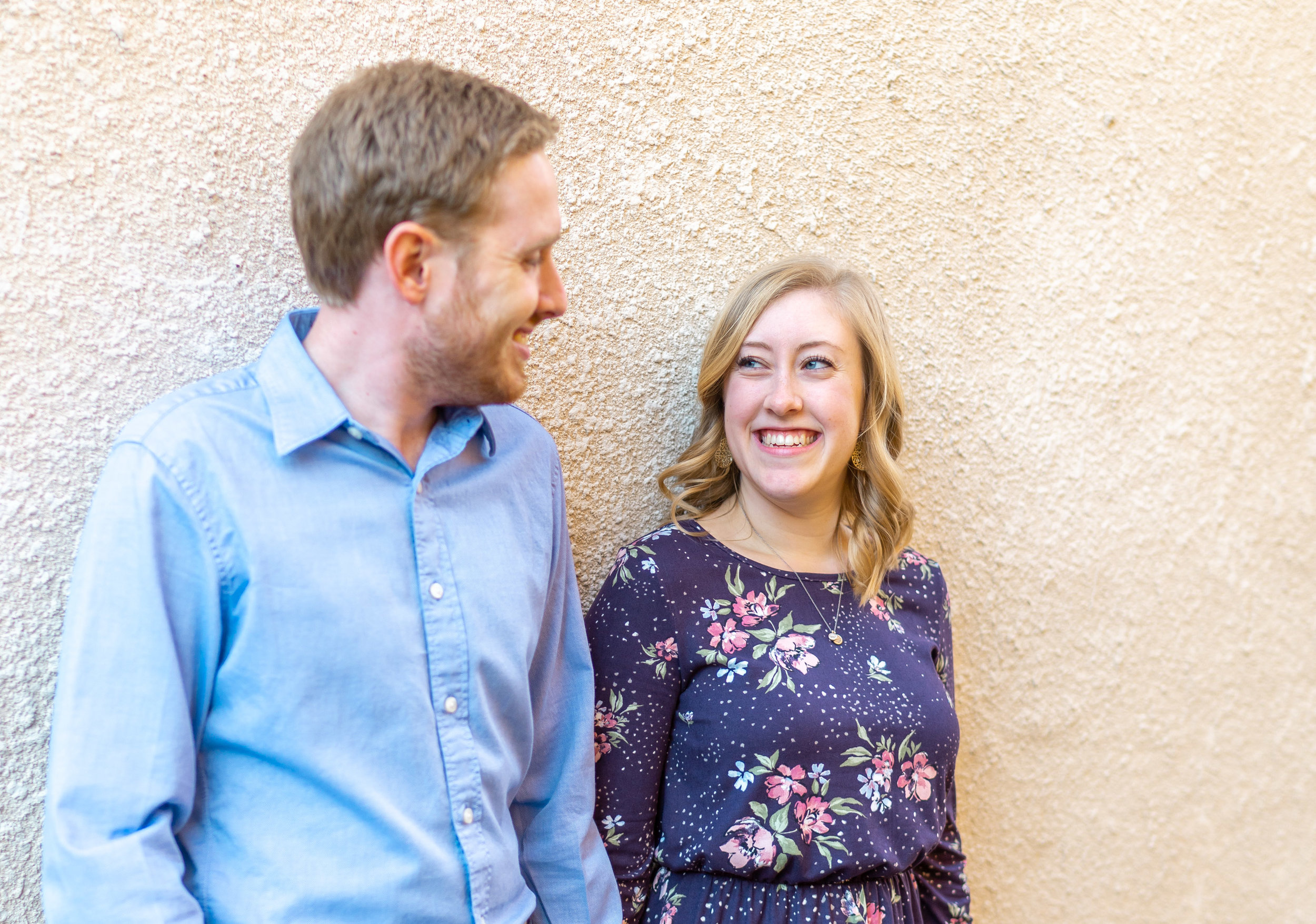 Bride and groom engagement session in front of stucco wall