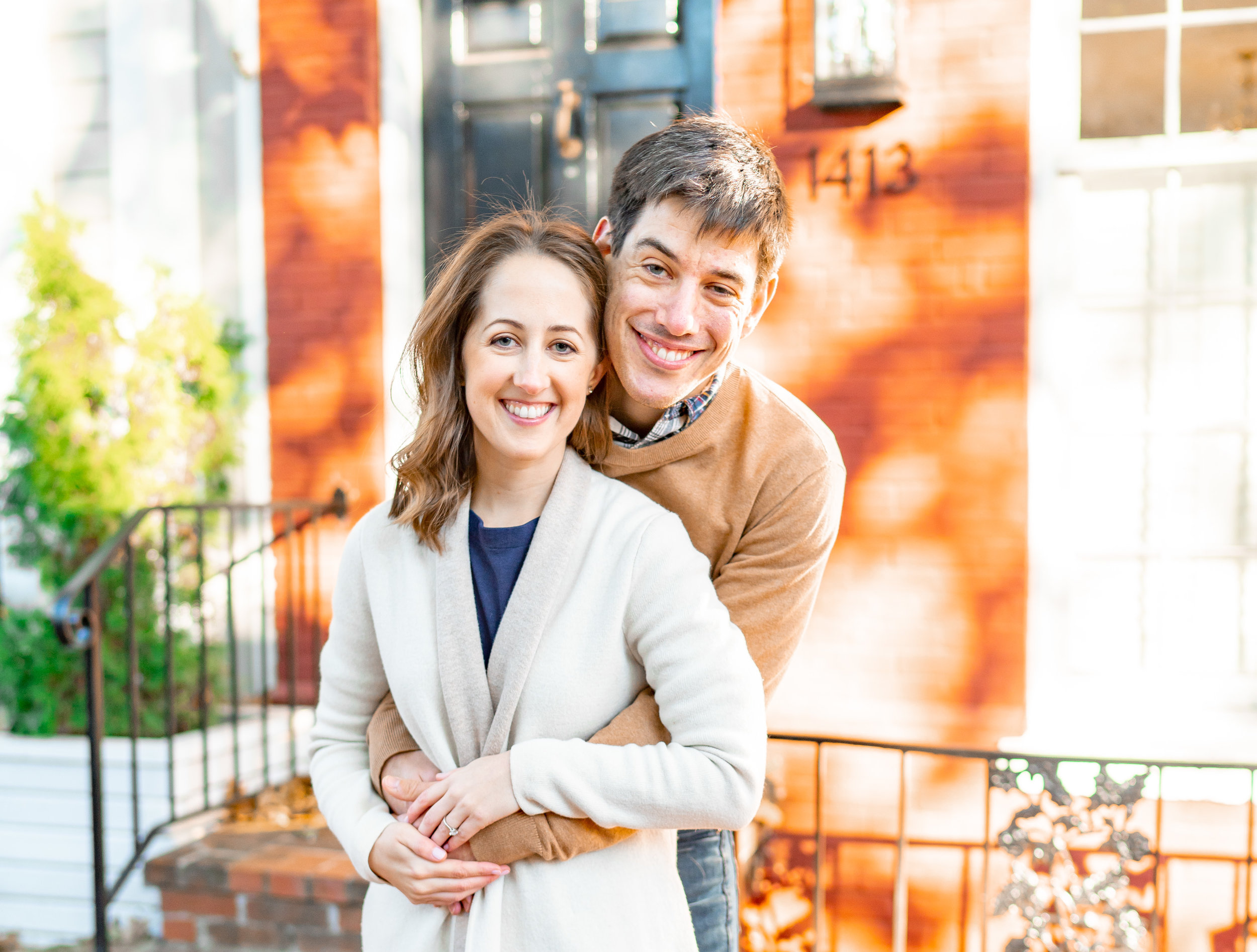 Bride and groom during engagement shoot in front of colorful Georgetown townhouses