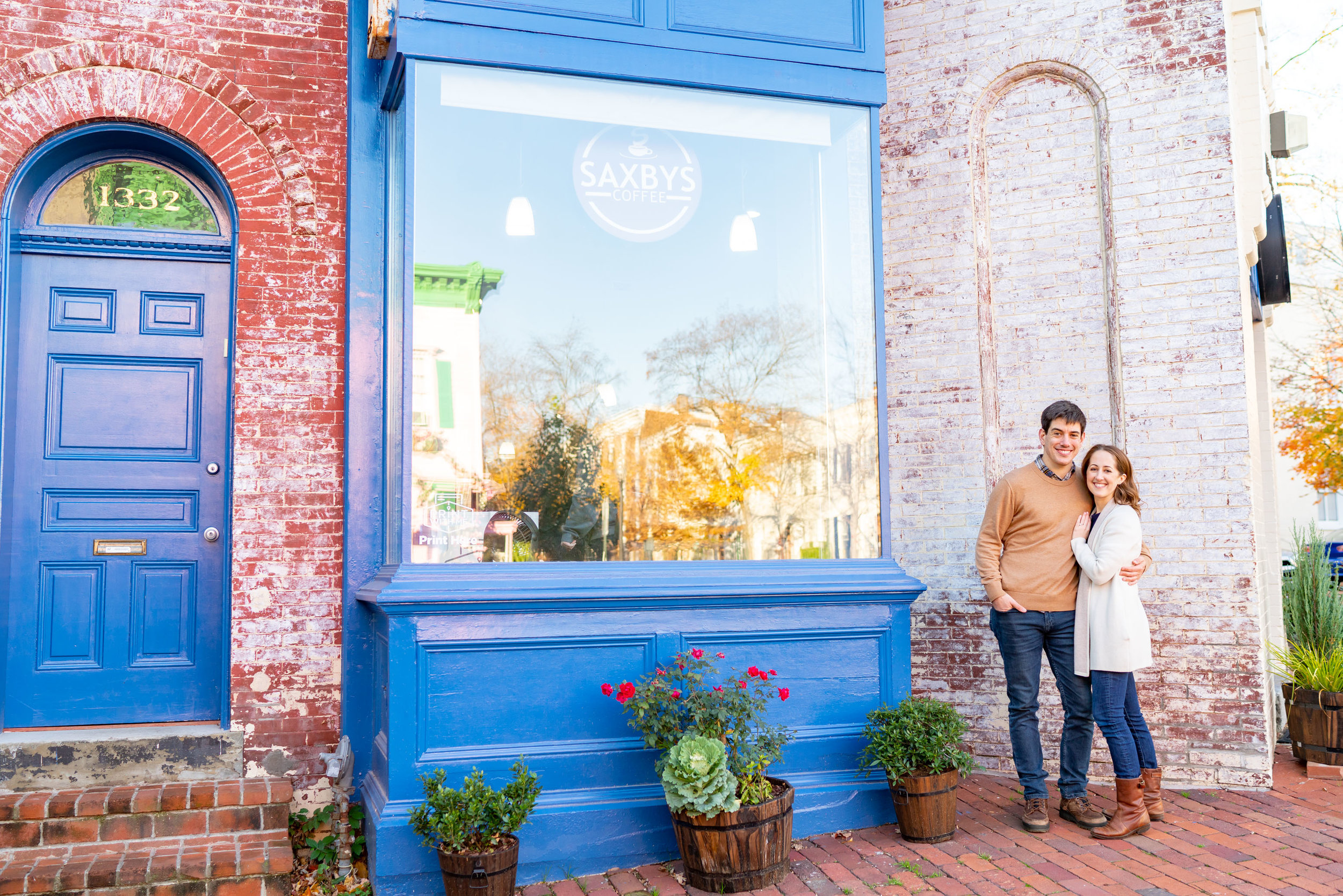 Bride and groom standing in front of blue front Saxby's coffee shop for engagement photo