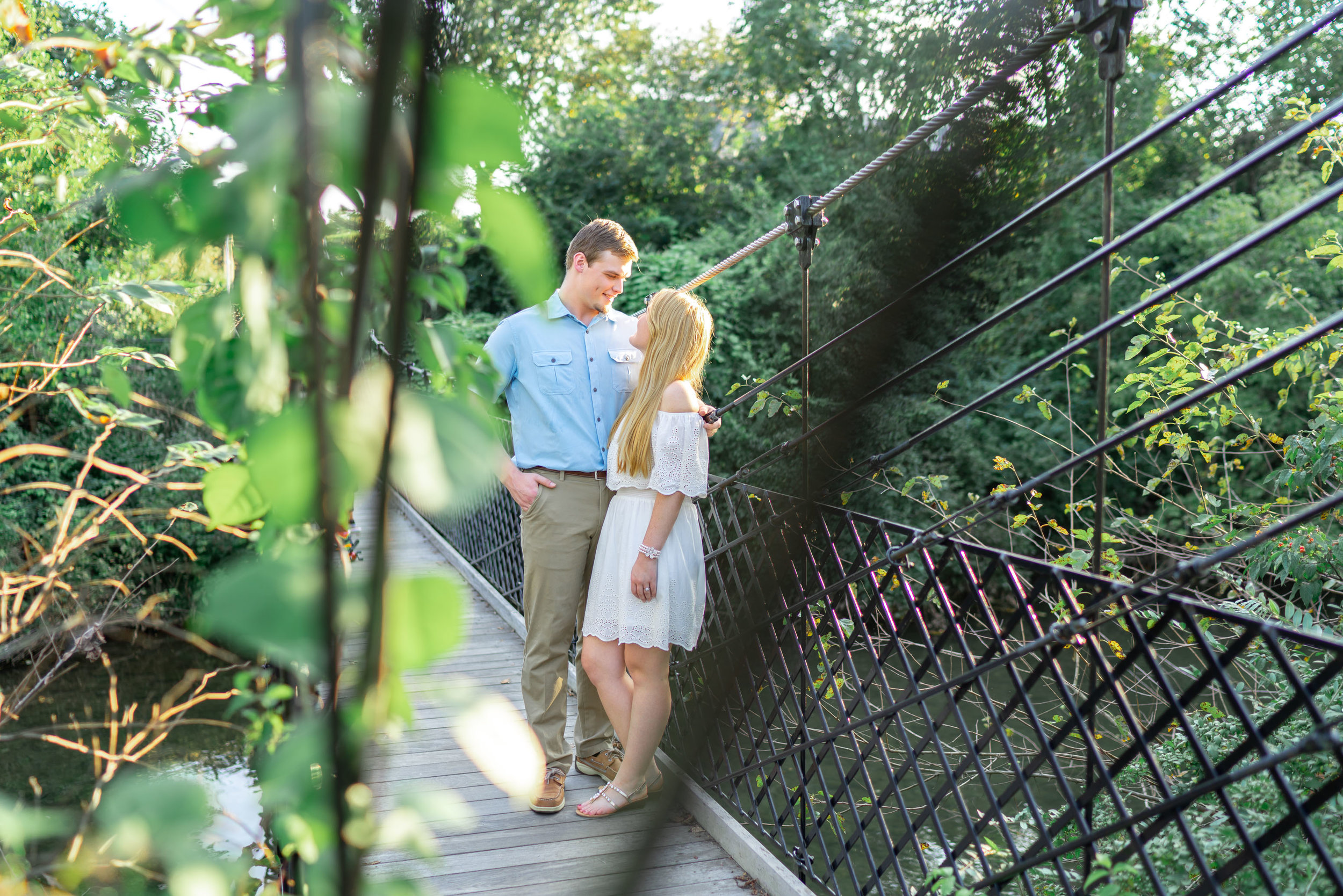 Baker Park suspension bridge engagement photo with bride and groom in summer