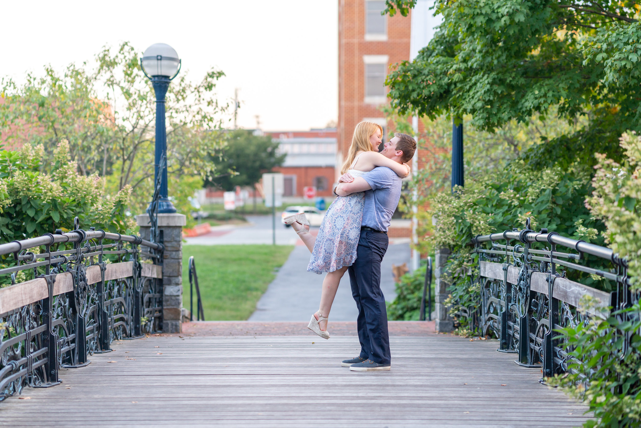 Groom lifting and kissing his bride on a bridge in Frederick Maryland downtown riverwalk