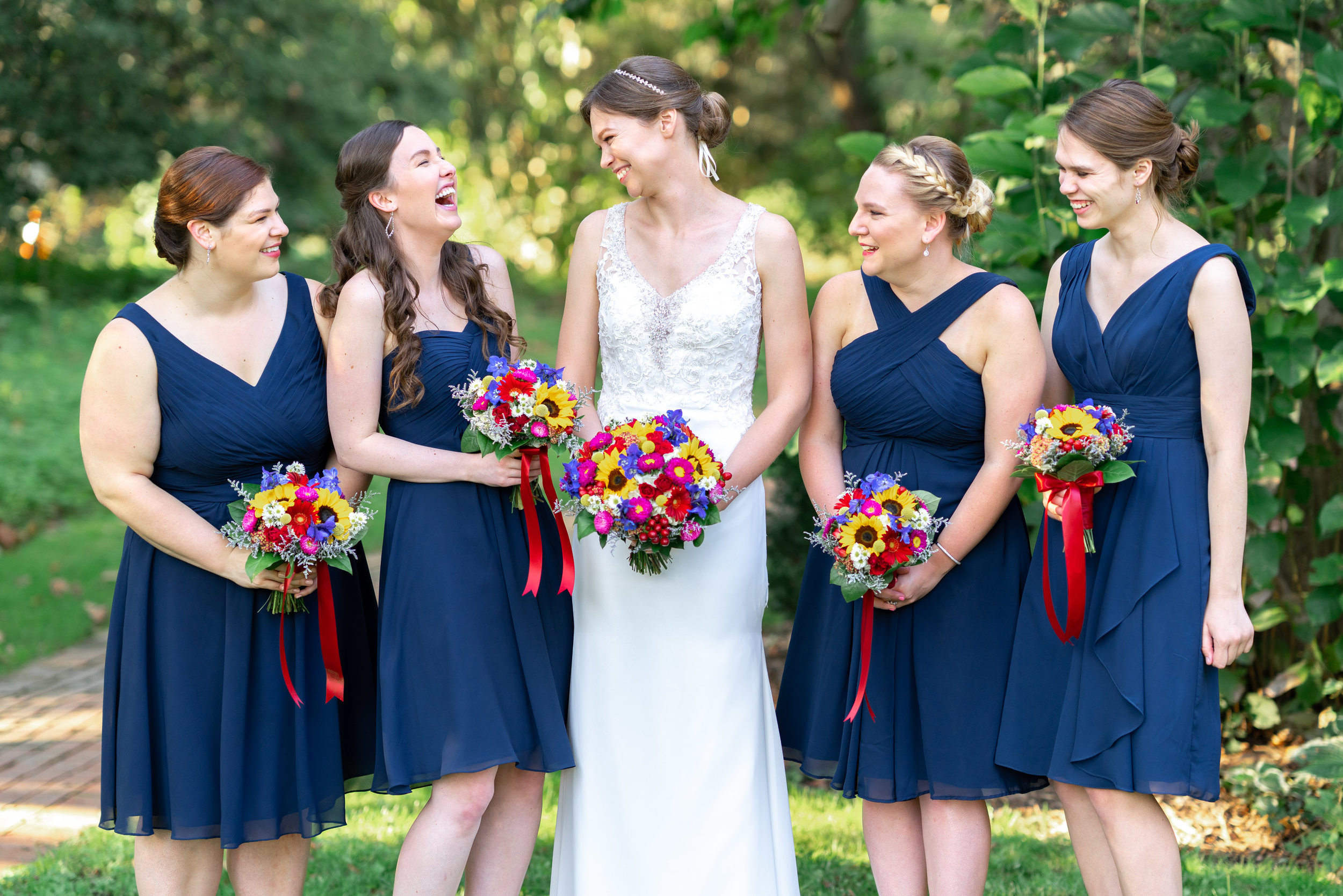 Bride in Morilee Myka and bridesmaids in navy Azazie at Elkridge Furnace Inn