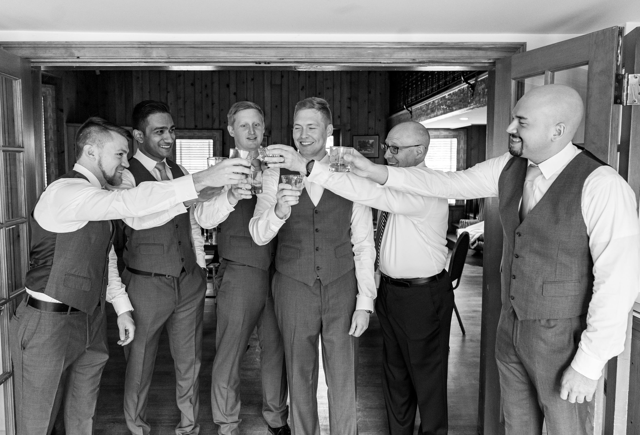 Groom and groomsmen toast in groom's suite at Rockville's Glenview Mansion wedding