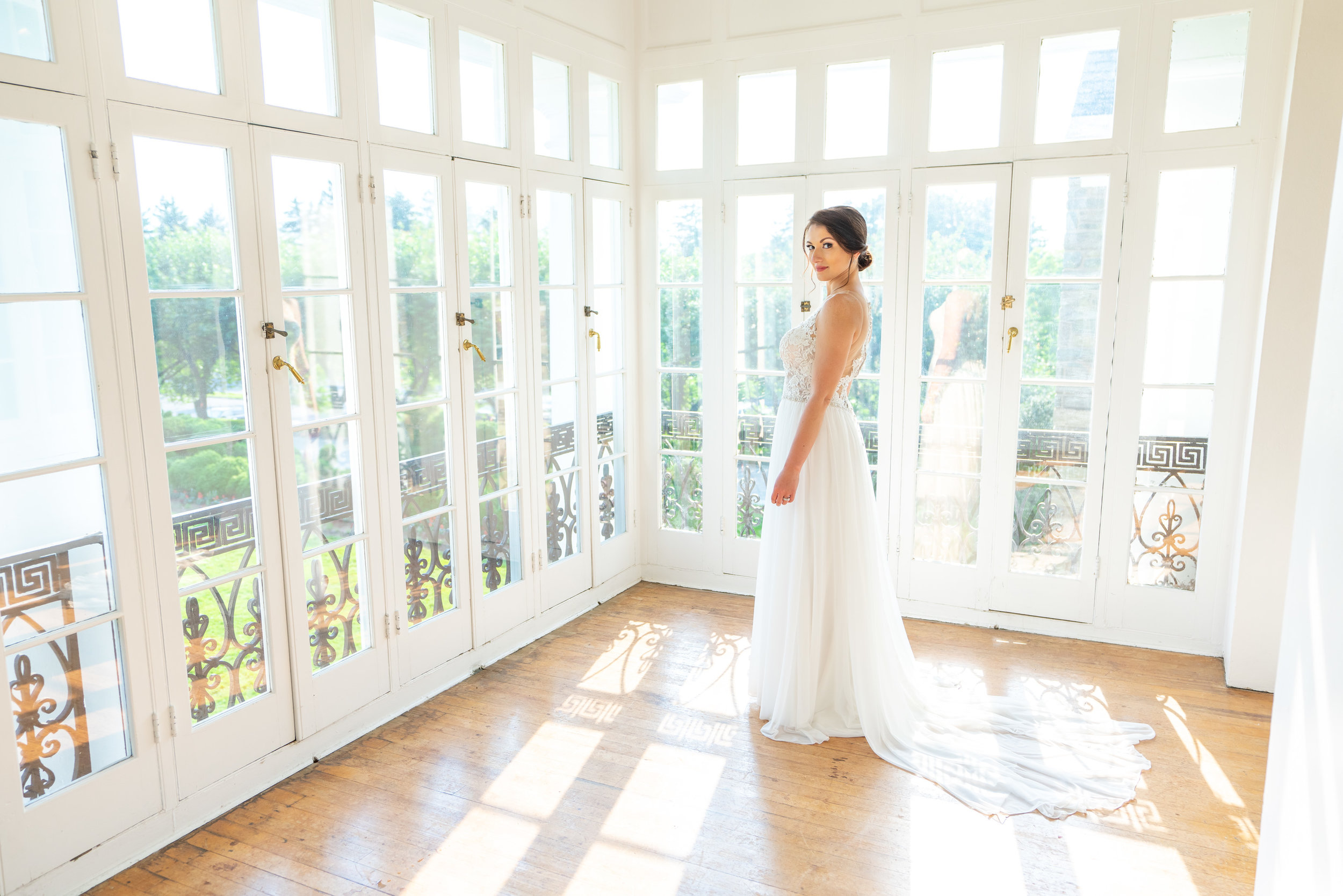 Bride standing in glass balcony overlooking Rockville's Glenview Mansion