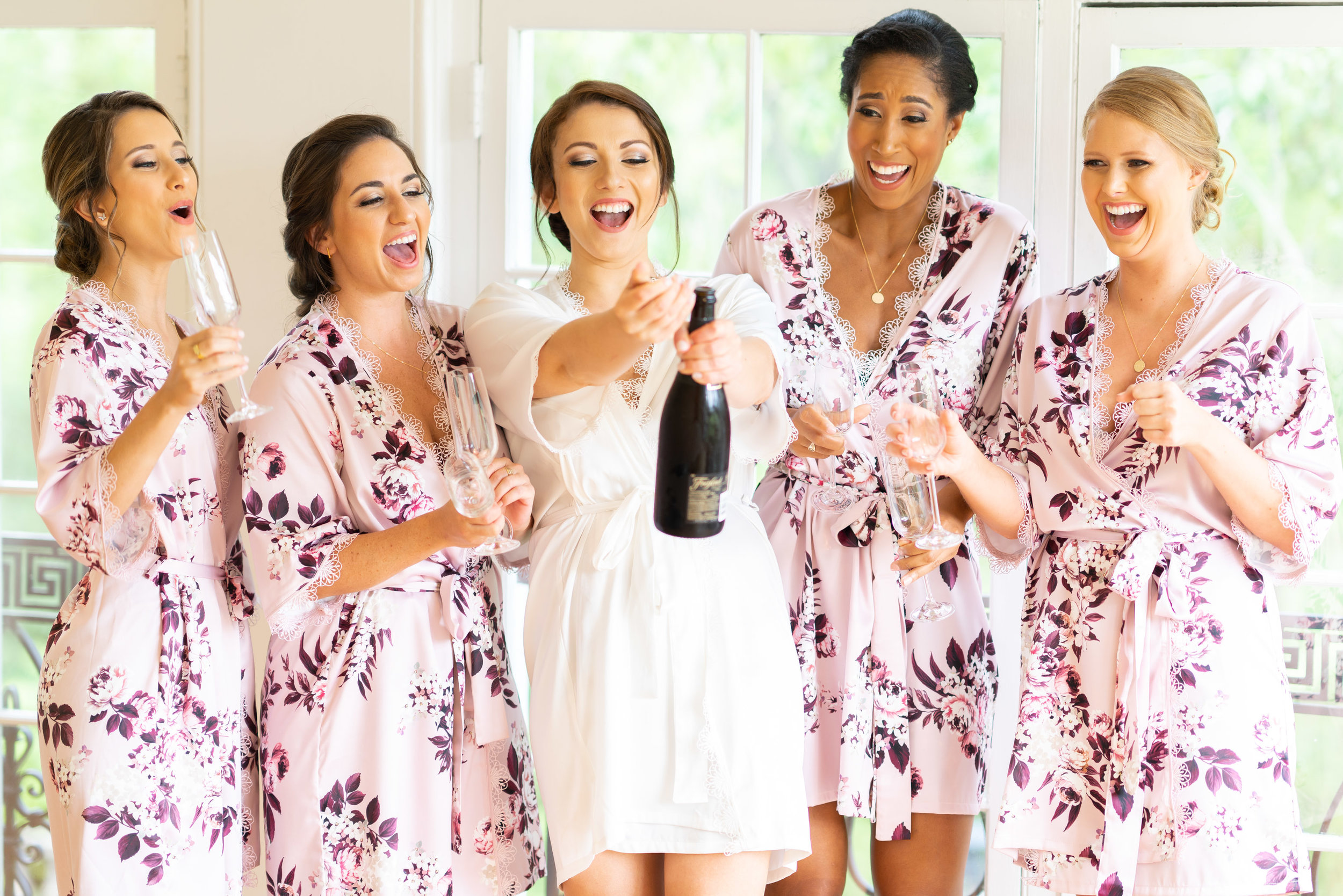Bridesmaids and bride pop champagne at Glenview mansion in Rockville