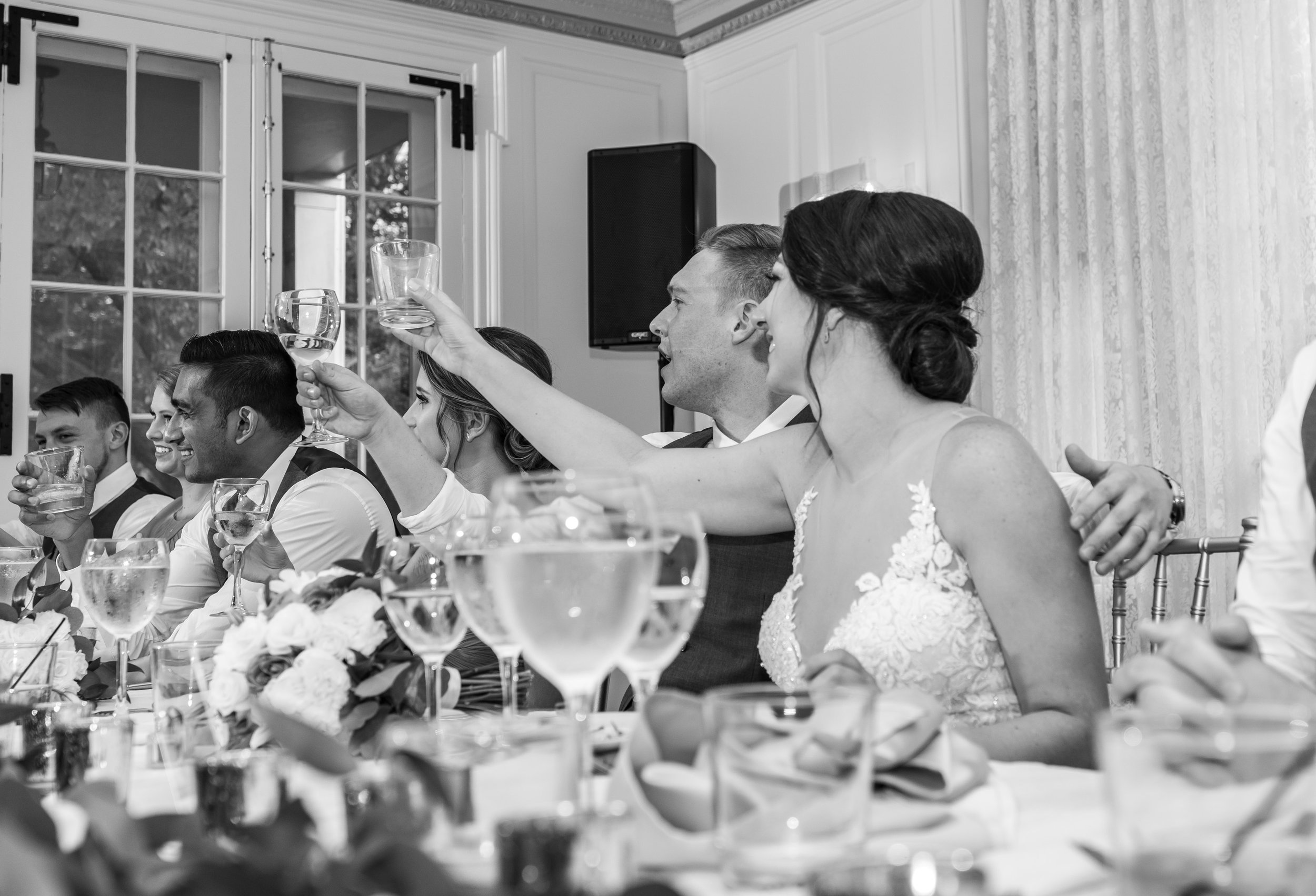 Bride and groom cheers their glasses to the bride's father at Glenview Mansion