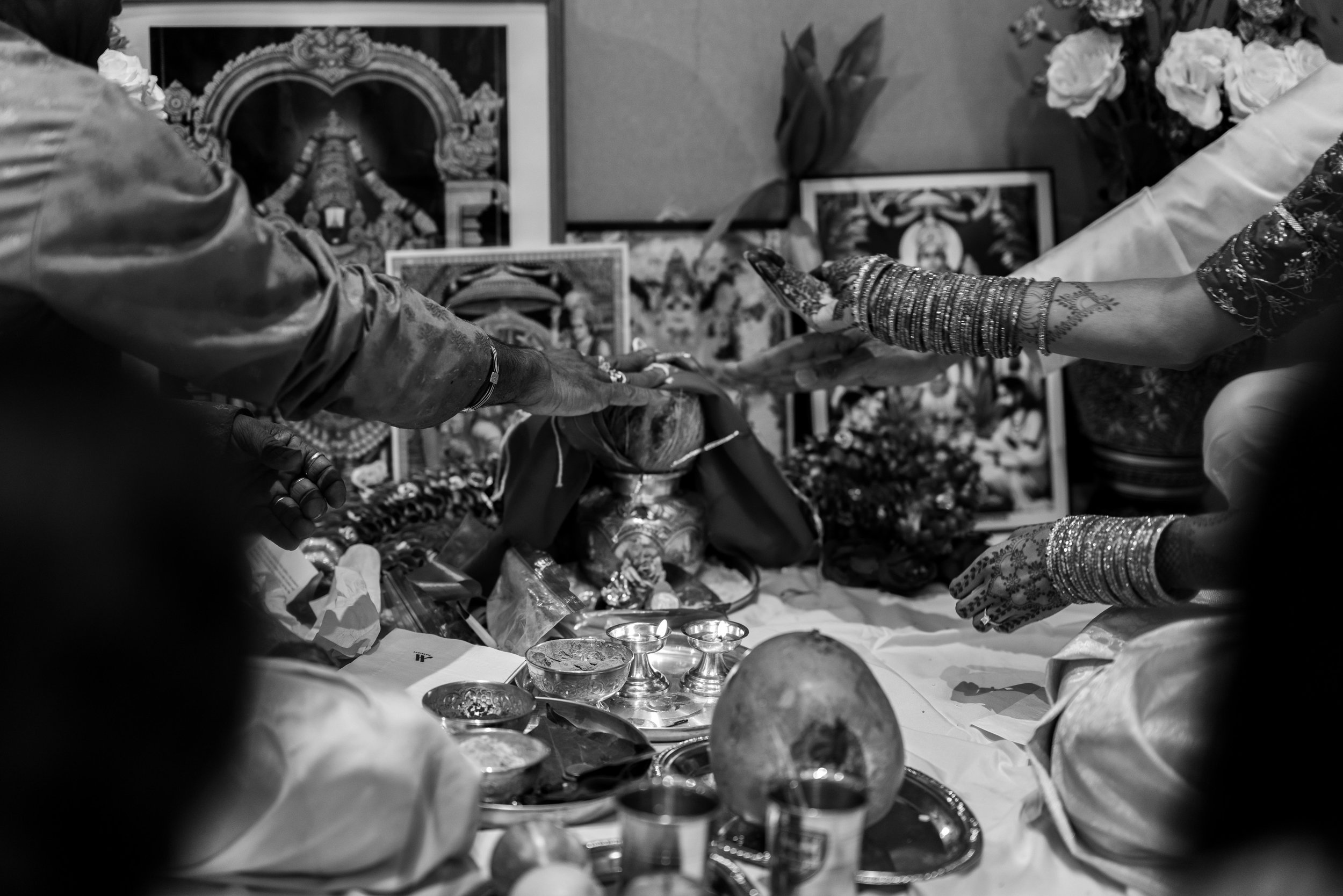 Black and white photo of hands during the indian puja wedding ceremony