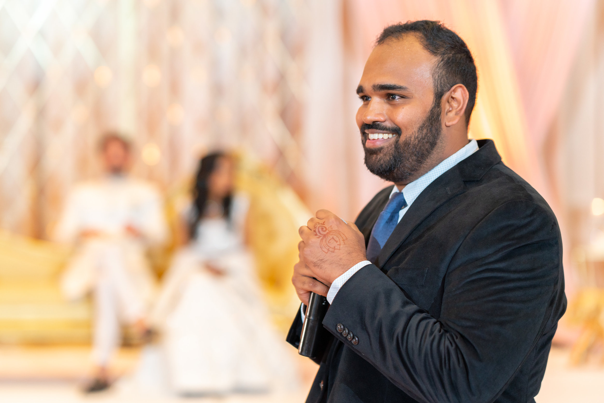 Bride's brother smiling and reading funny toast during indian wedding reception