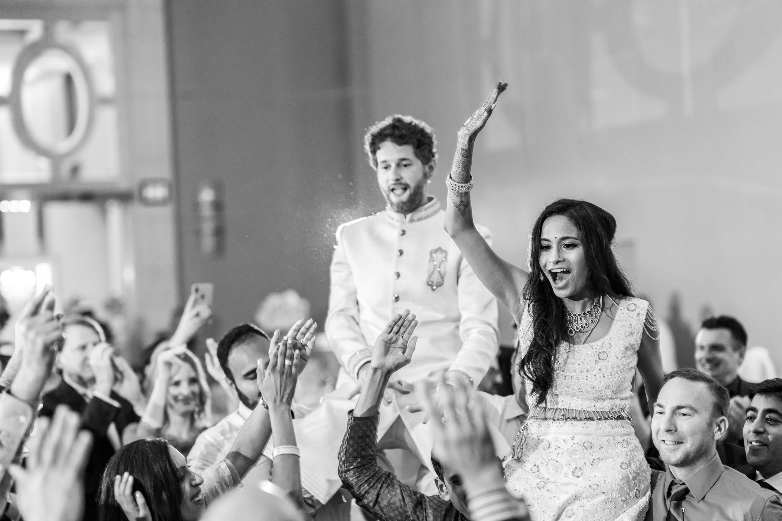 Bride and groom lifted in the crowd at indian wedding reception in maryland
