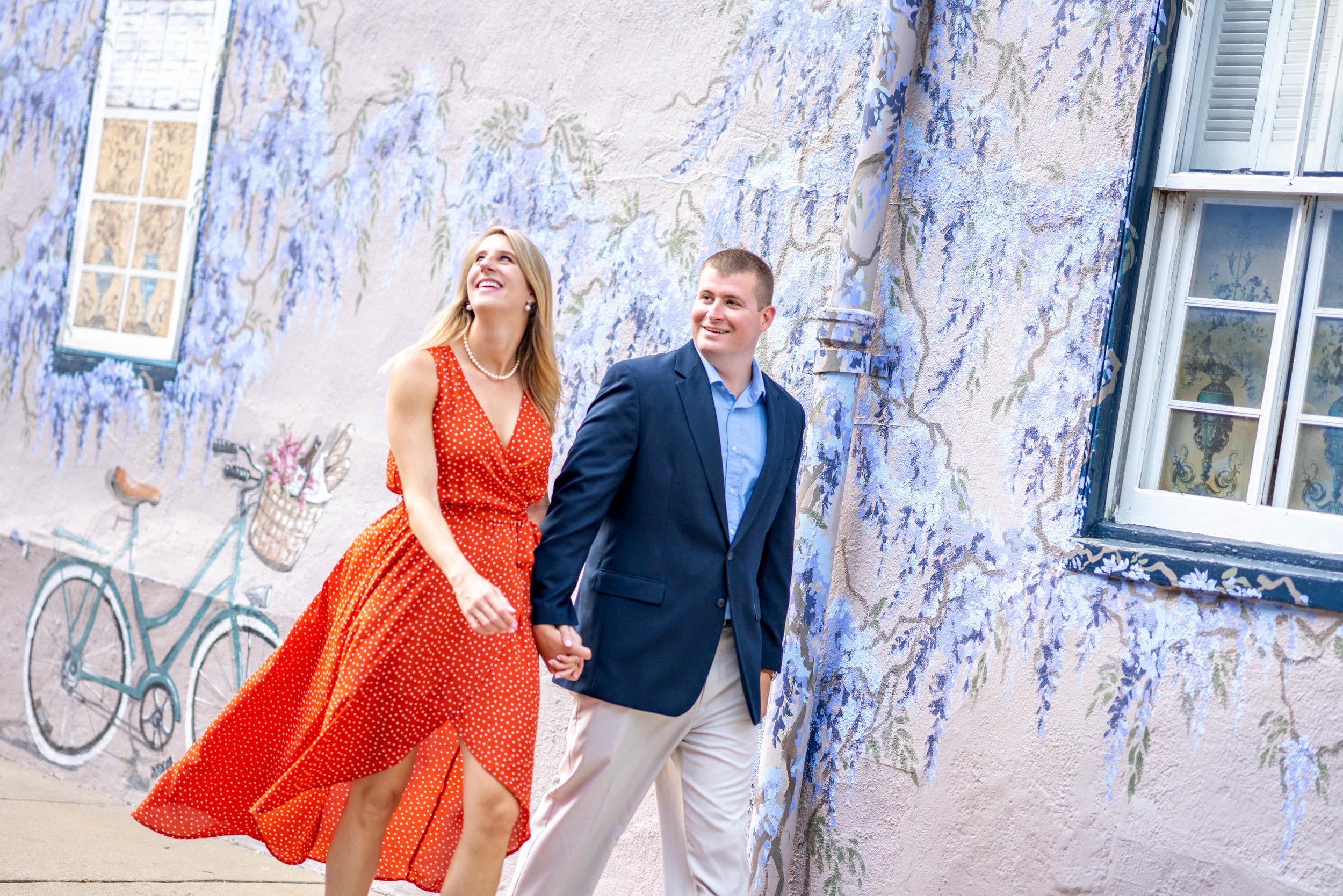 Couple walking past purple grape wisteria street mural in Annapolis