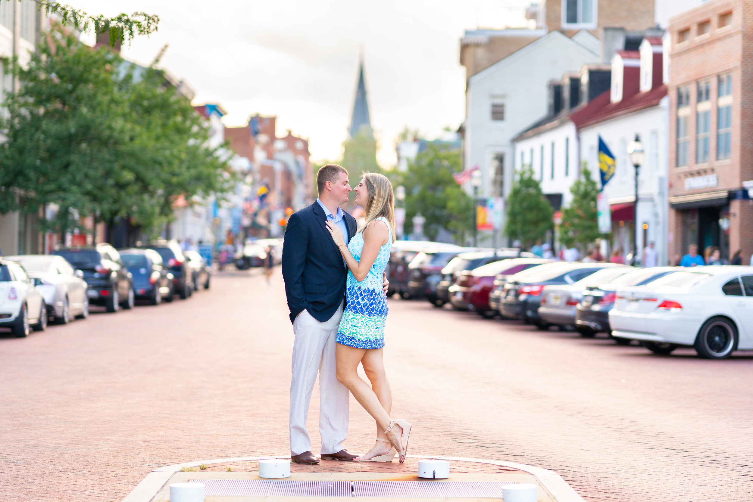 Couple standing in middle of downtown annapolis street during sunset engagement photos