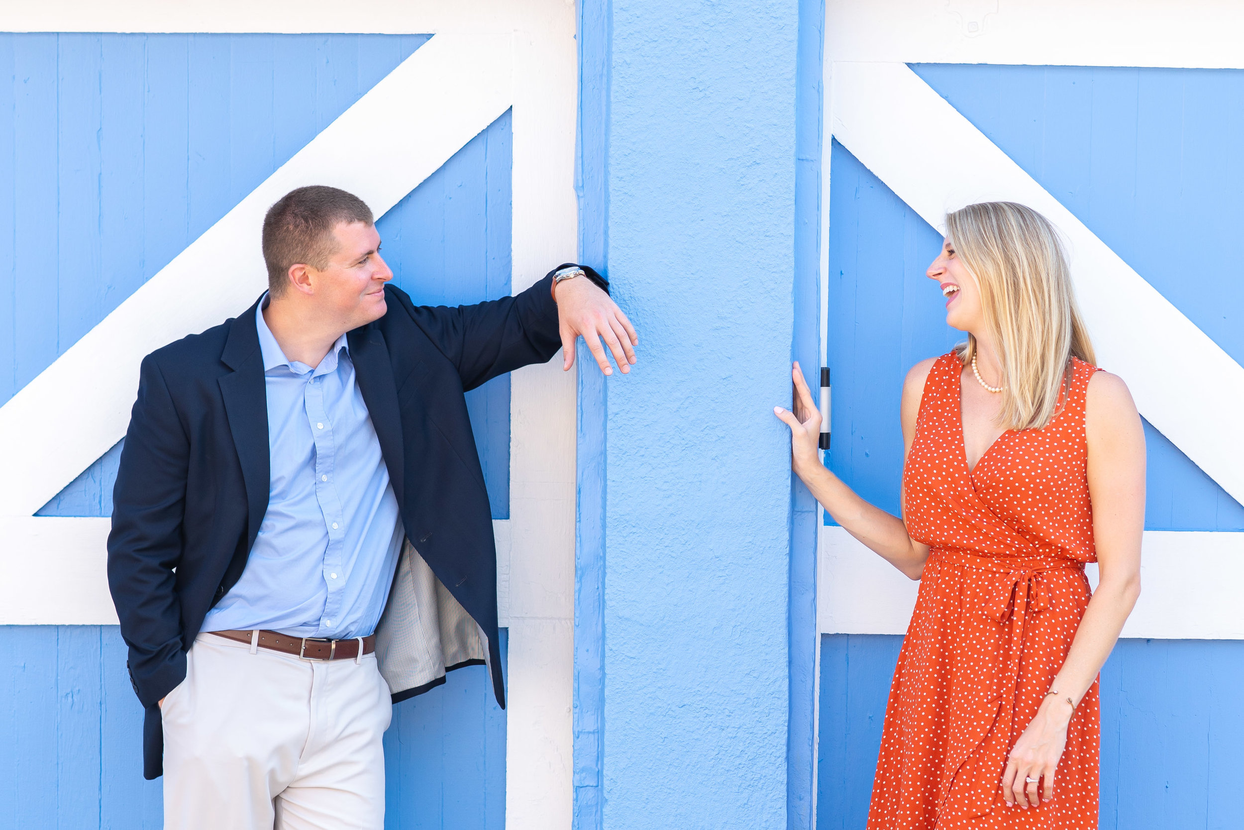 Couple laughing in front of blue wall for engagement photos in annapolis md