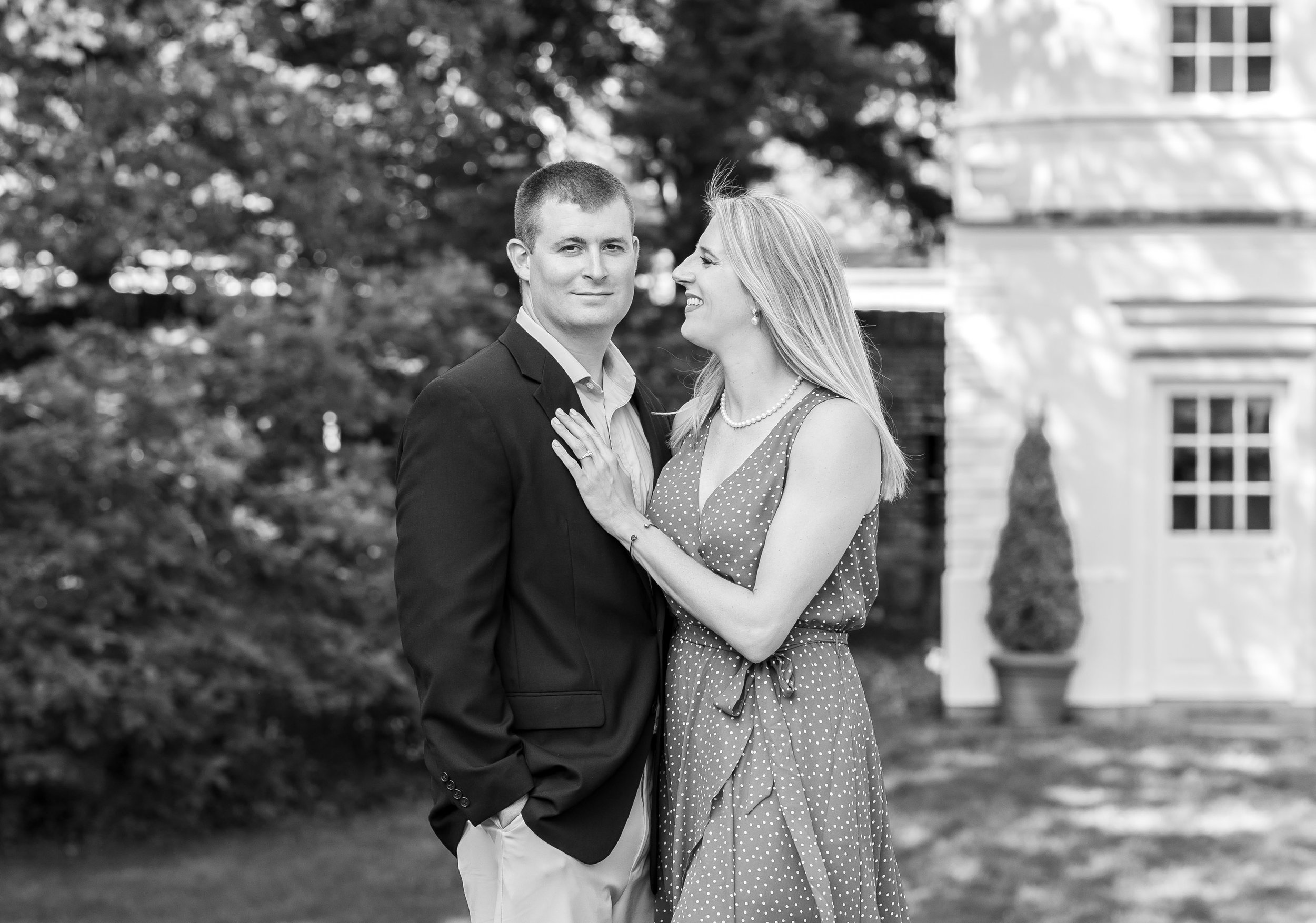 Black and white engagement photo of bride and groom posing in William Pac House gardens