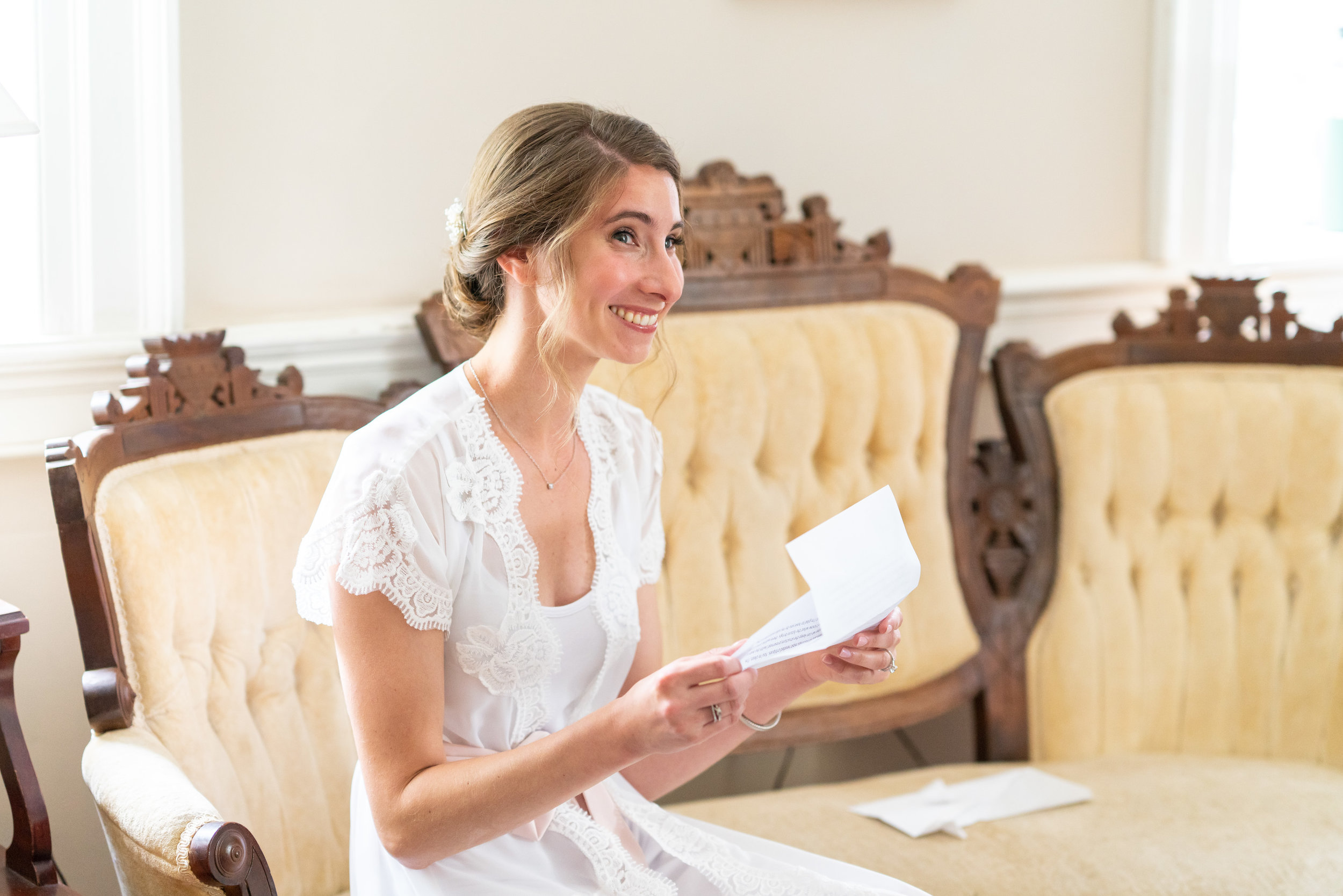 Bride in bhldn bridal robe reading a card from her groom in bridal suite at Springfield Manor