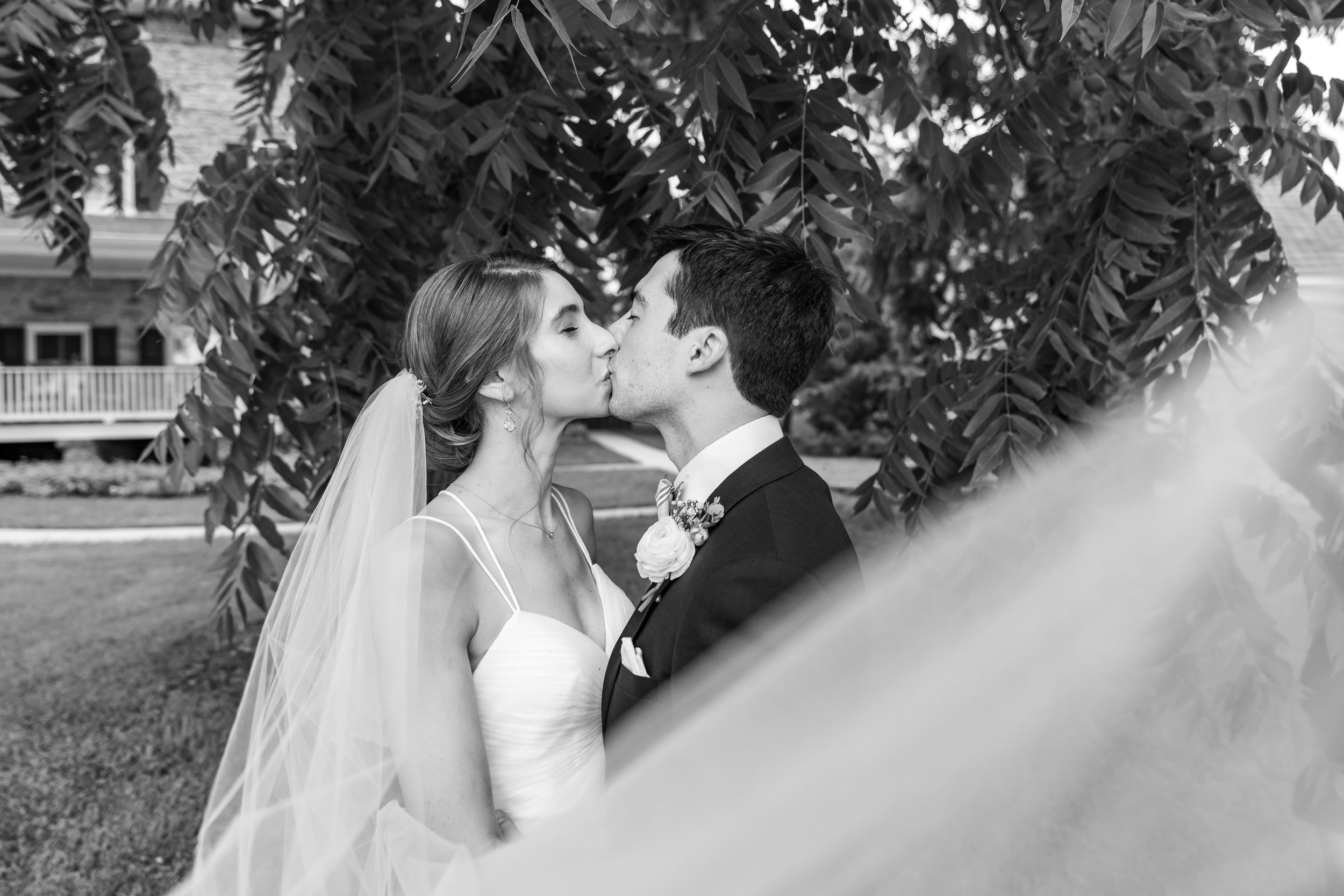 Bride and groom black and white photo kissing beneath veil from Lovely Bride