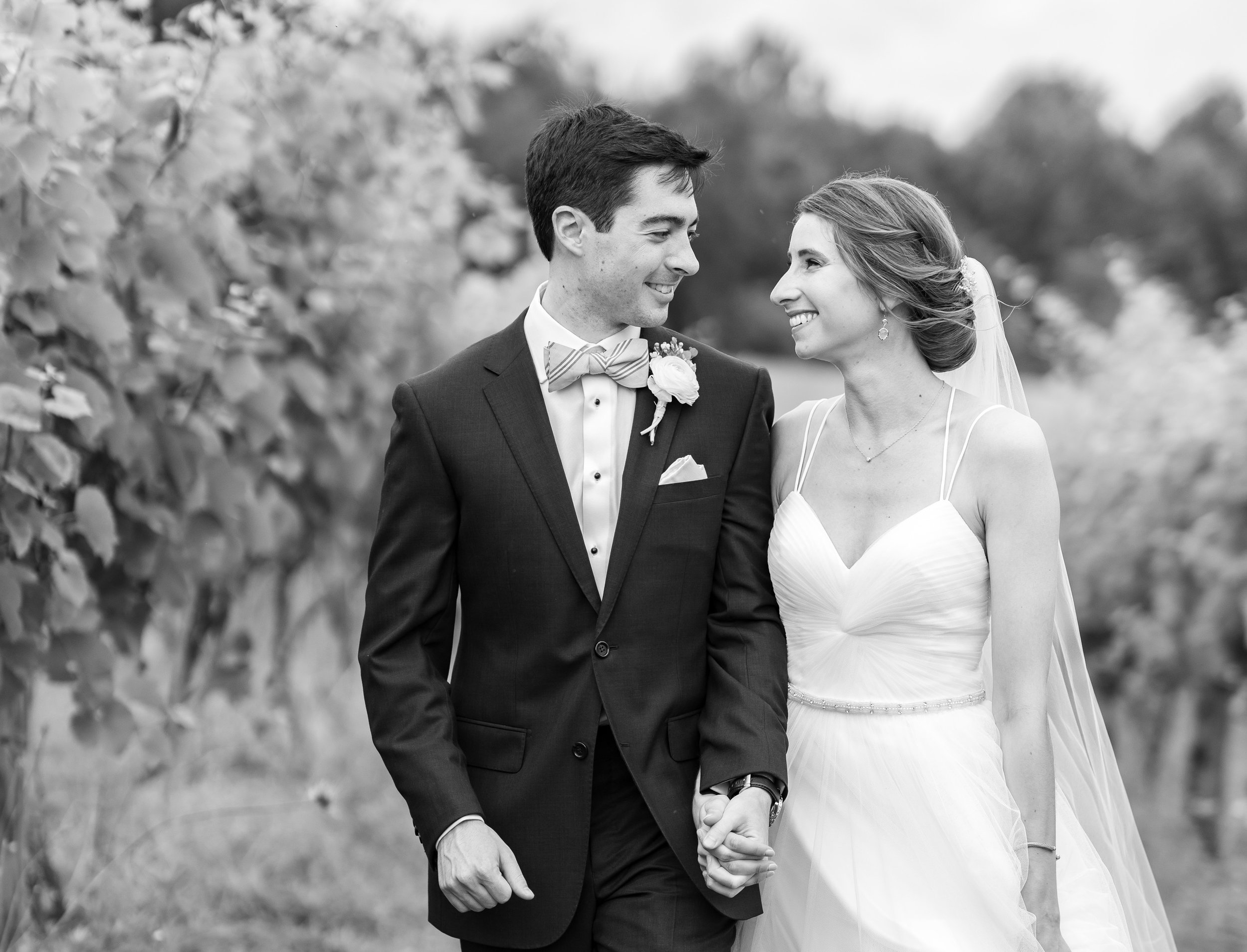 Black and white photo of bride and groom walking through a vineyard in Theia gown and J Crew suit